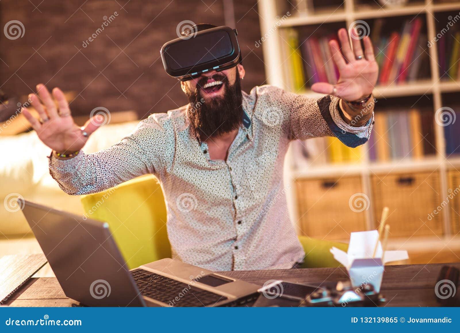 Brodaty młody człowiek jest ubranym rzeczywistość wirtualna gogle