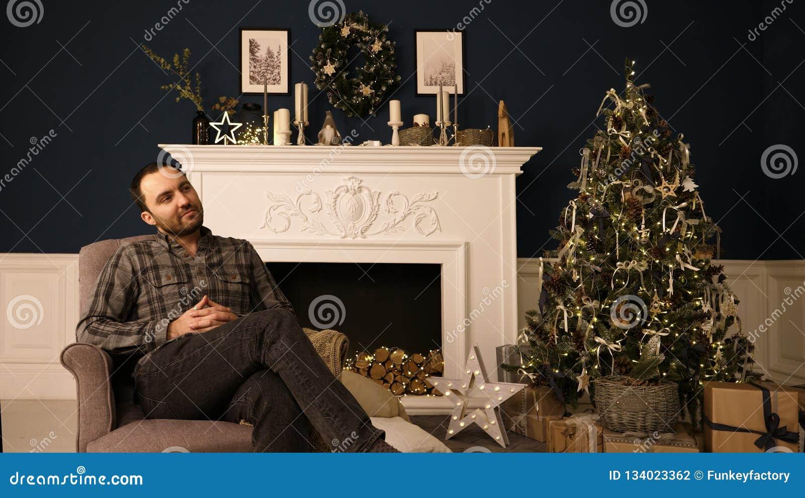 Brodaty przystojny modnisia młody człowiek w Bożenarodzeniowy roomthinking prezentów pomysły rojenie