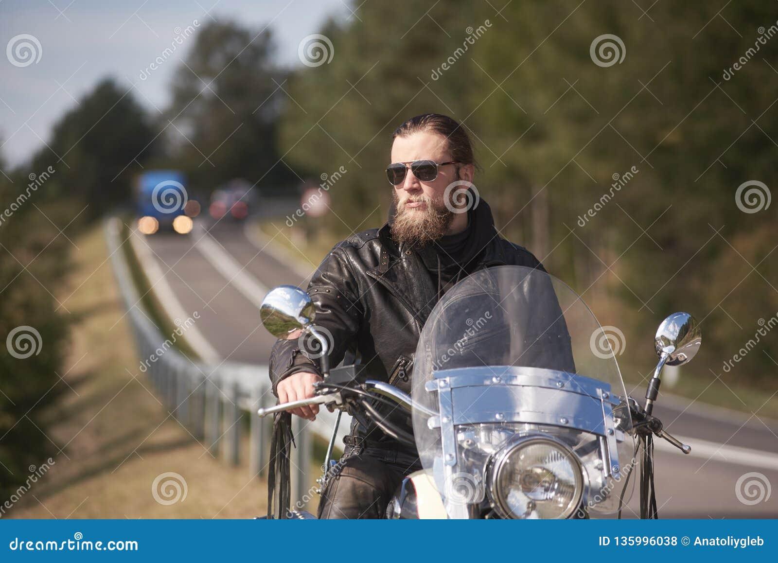 Brodaty rowerzysta z długie włosy w czarnym skórzanej kurtki obsiadaniu na nowożytnym motocyklu