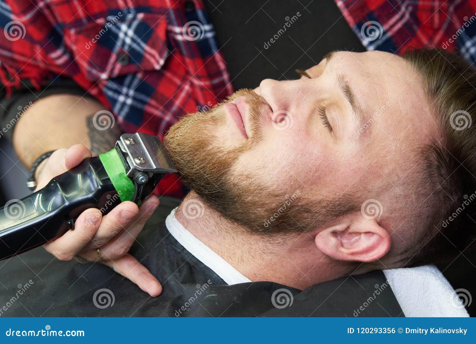 Brody opieka mężczyzna podczas gdy żyłujący jego twarzowego włosy ciie przy zakładem fryzjerskim