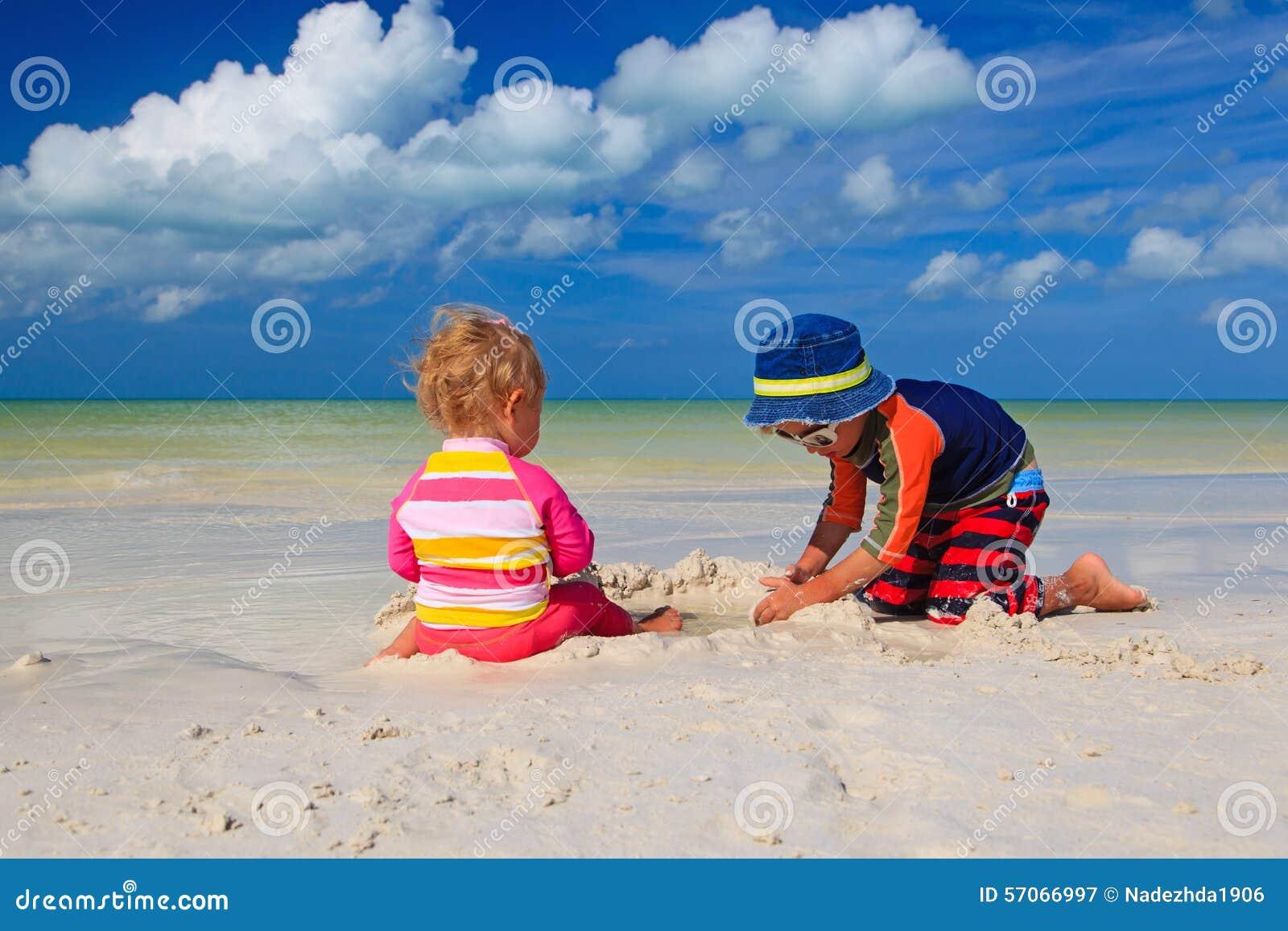 Broer en zuster het spelen met zand op strand