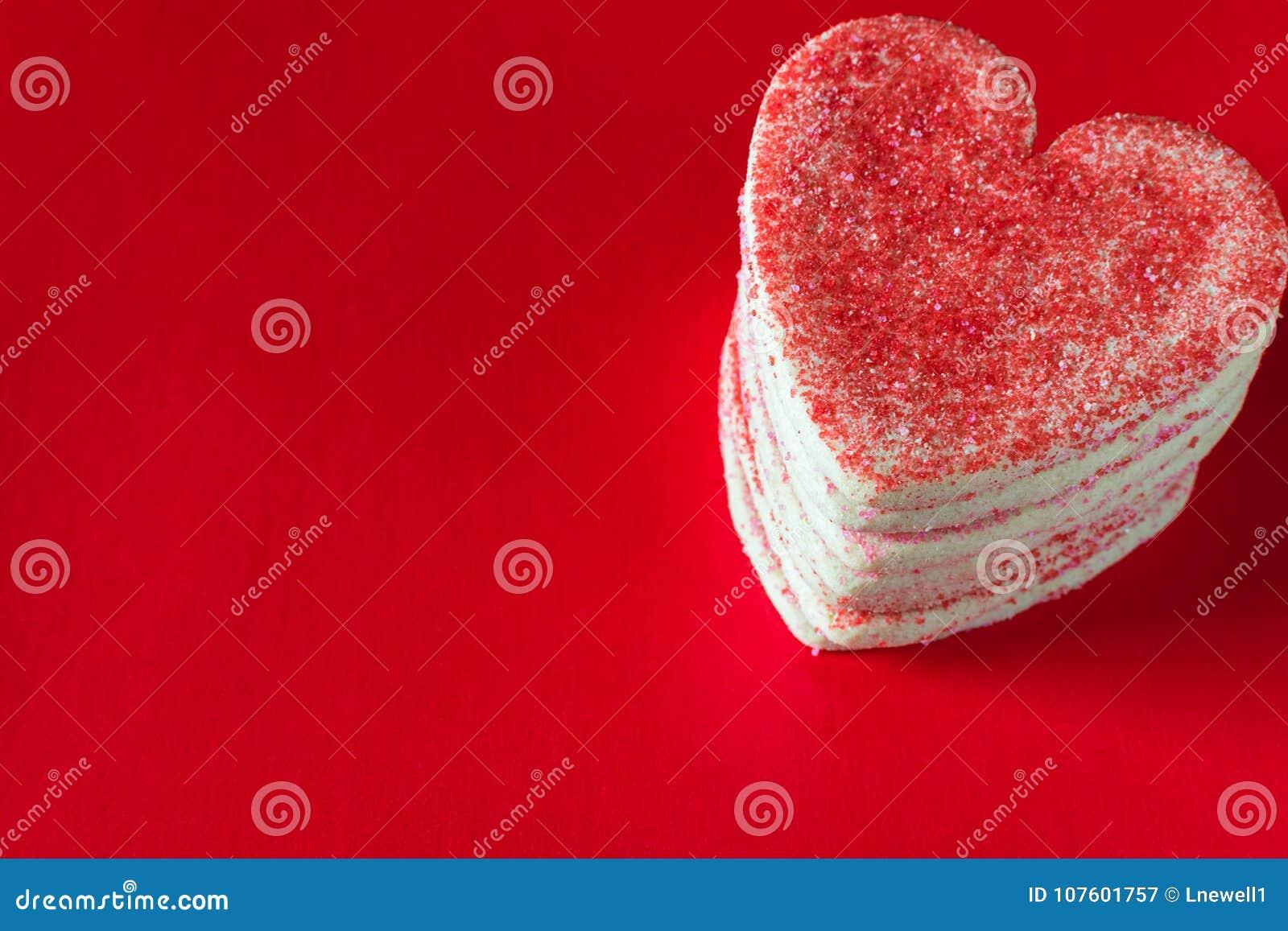 Brogujący serce kształtował valentines ciastka na czerwonym tle
