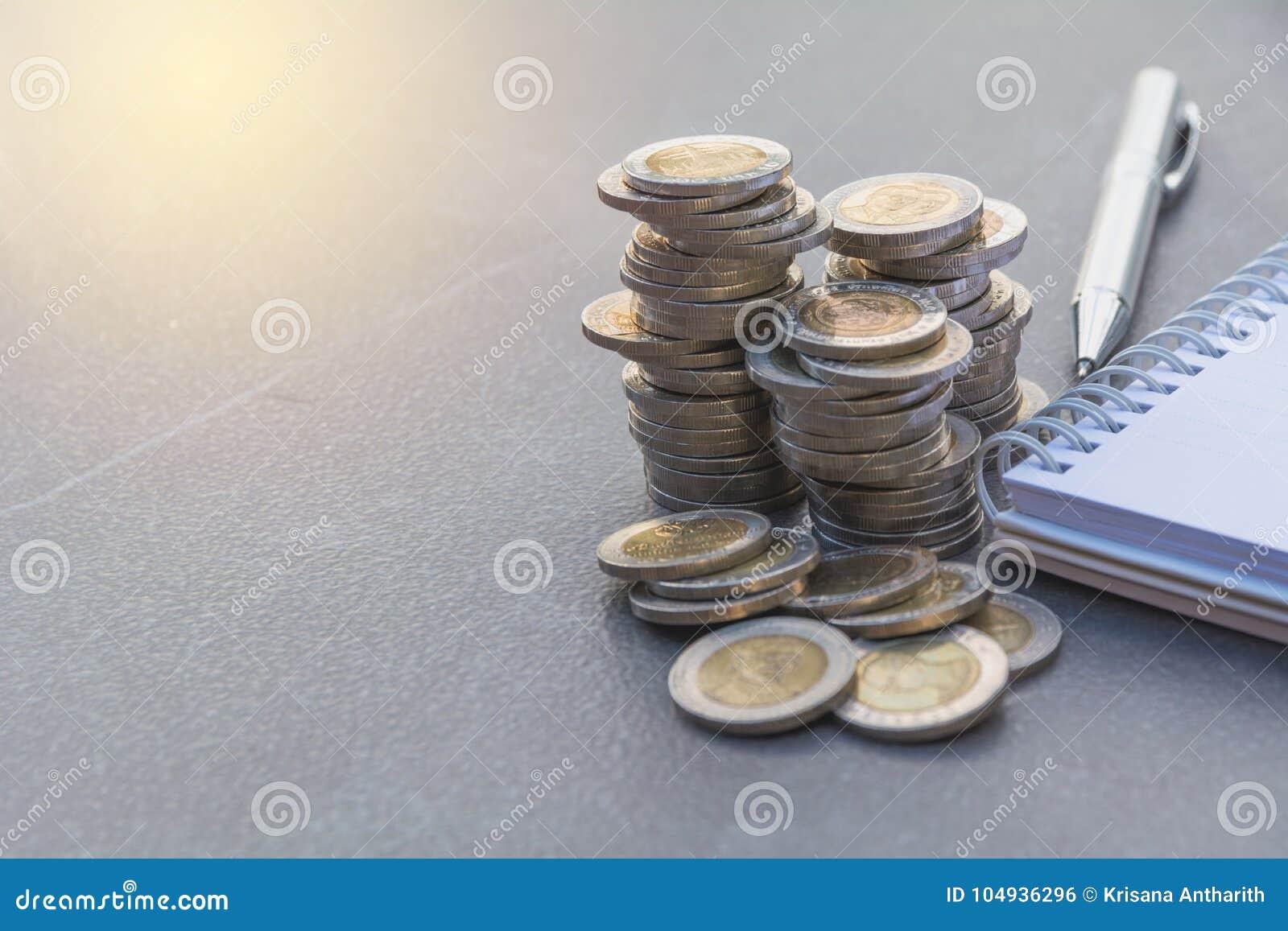Broguje monetę z piórem i nutową książkę na stole Pieniężny, accountin