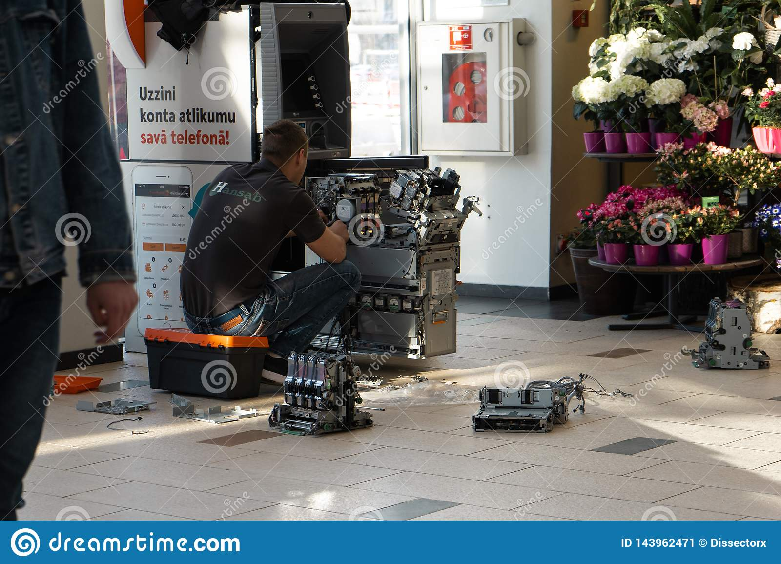 RIGA, LATVIA - APRIL 4, 2019: Broken ATM machine is being repaired - Bank are in a shopping centre