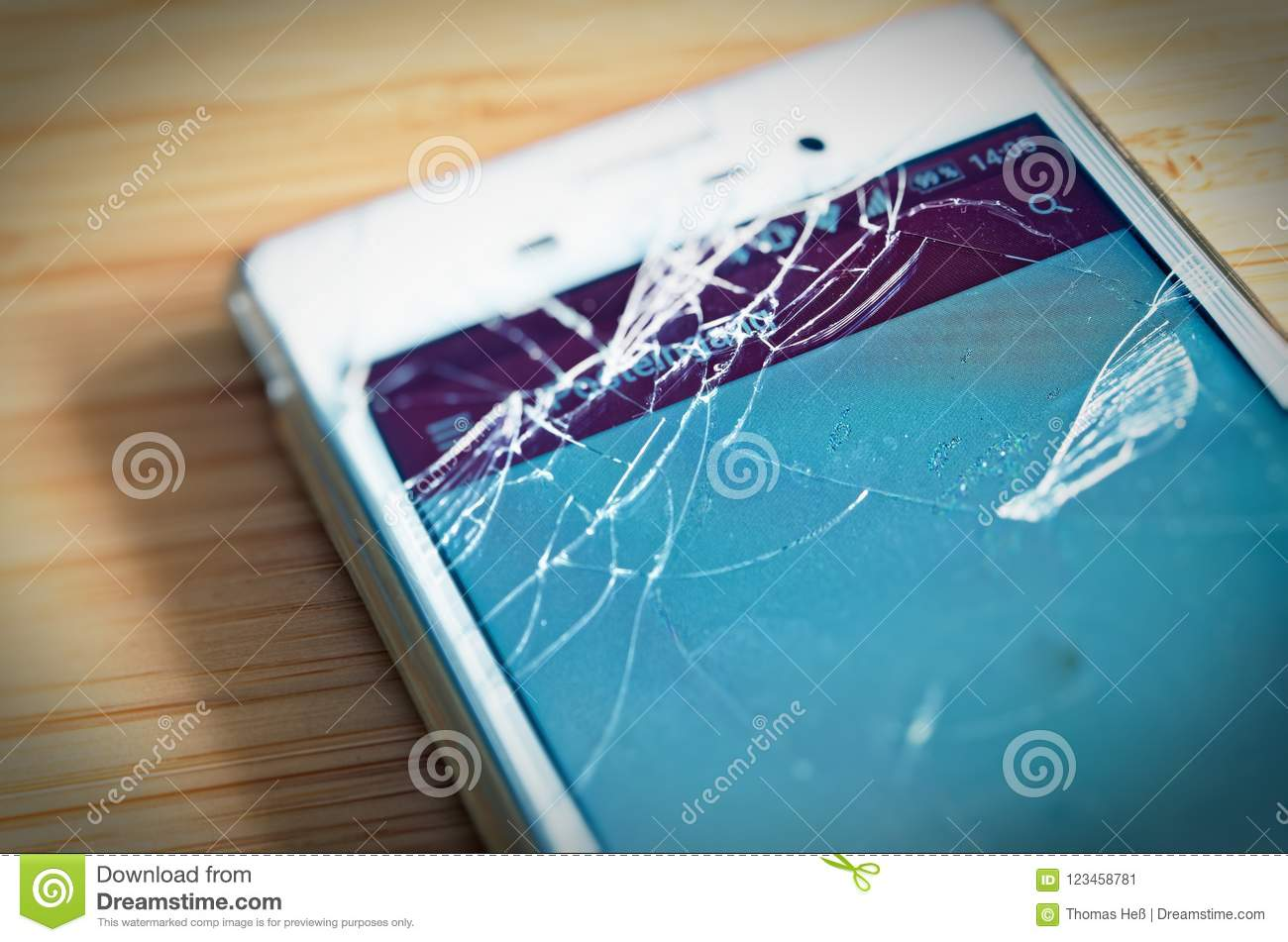 Broken cell phone with display damage and splintered display to symbolize damage to the phone display