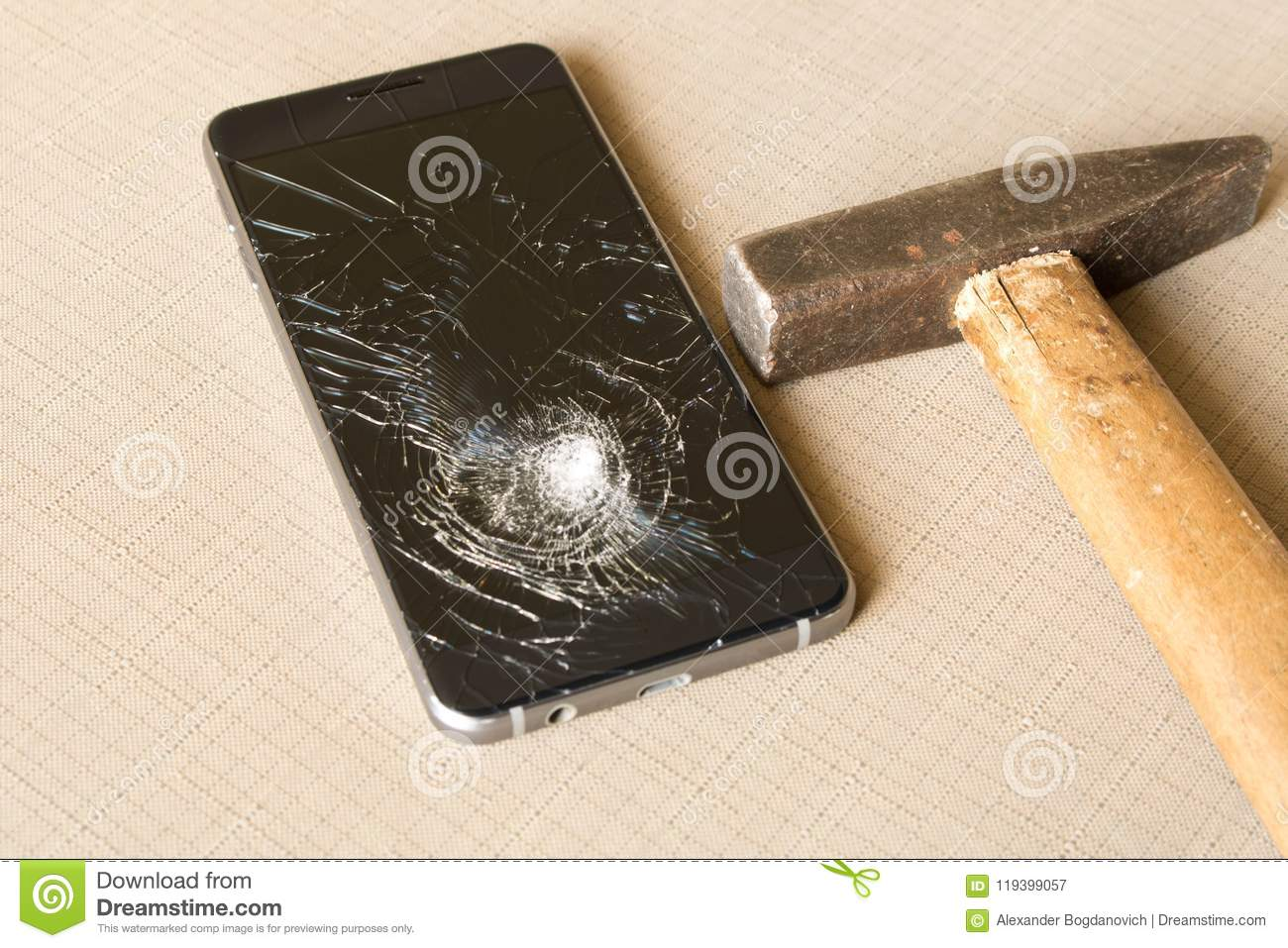A broken cell phone and hammer on grey background