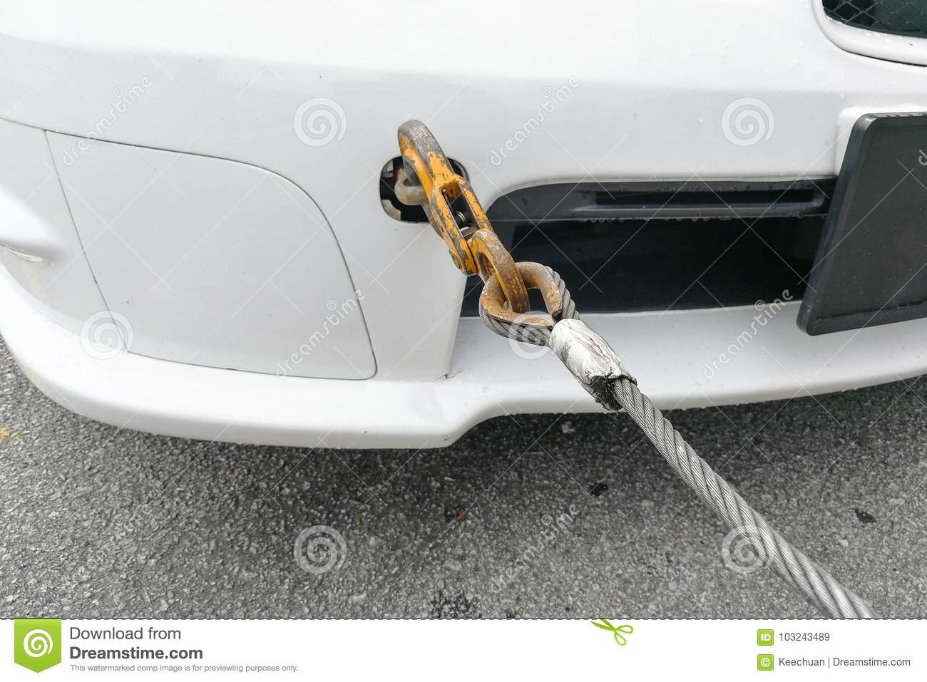 Broken down car fitted with hook and chain being towed