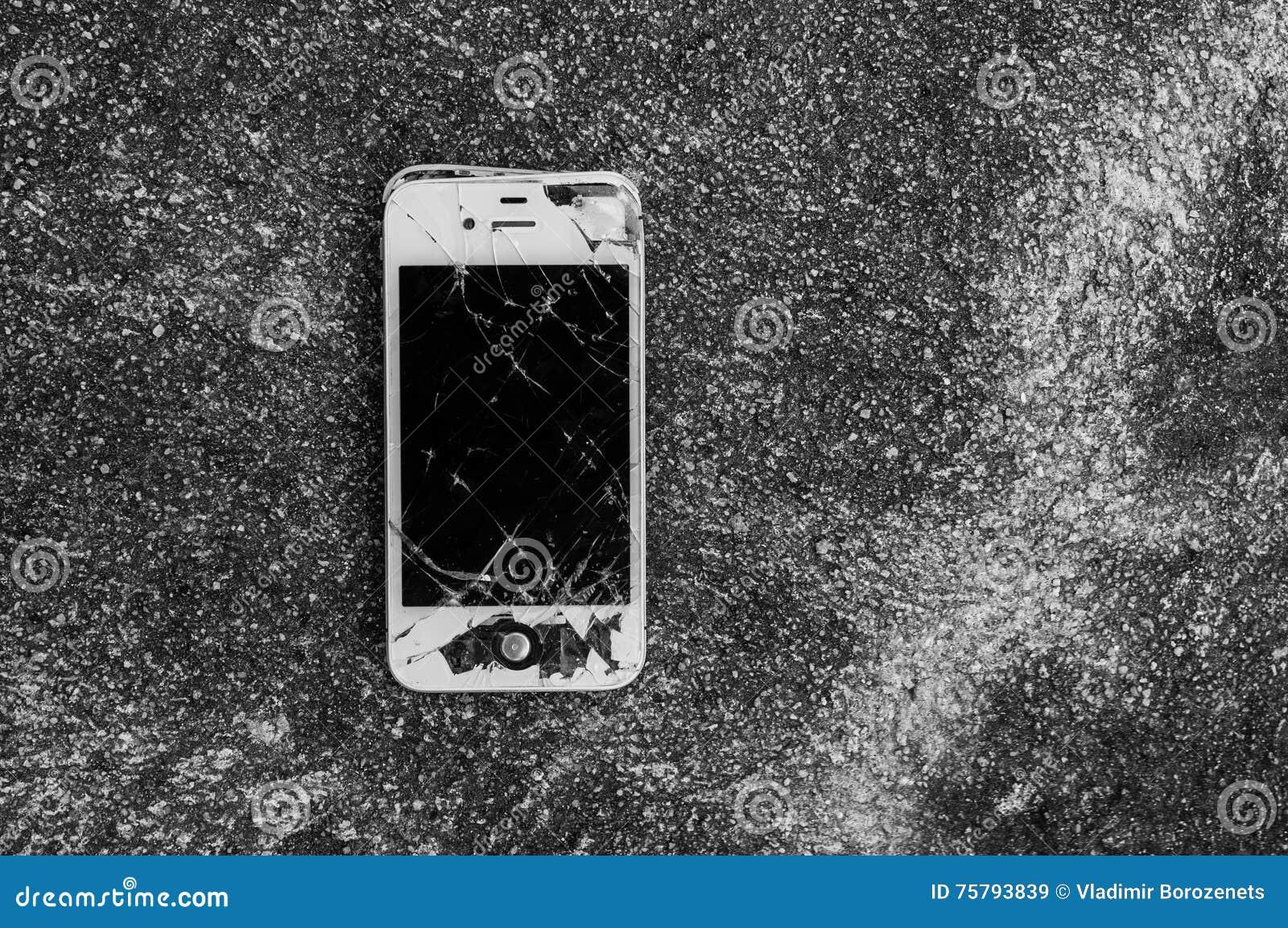 Broken iPhone 4S on asphalt road