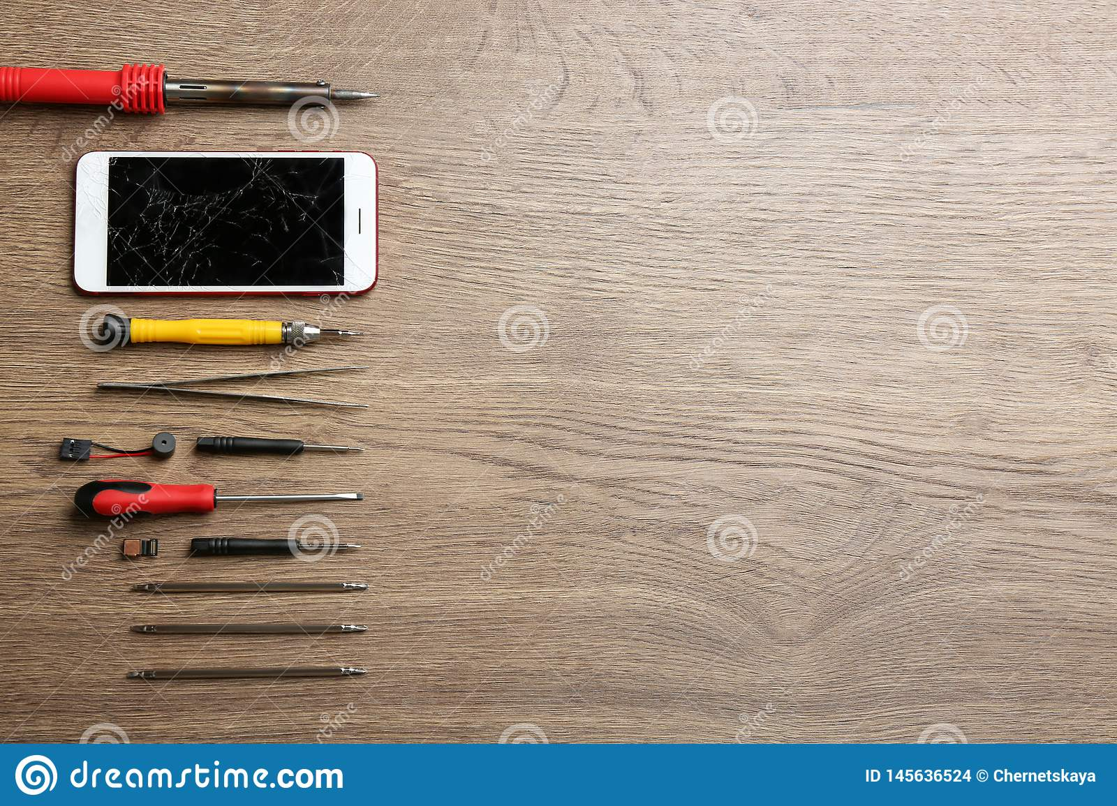 Broken mobile phone and repair tools on wooden table, flat lay.