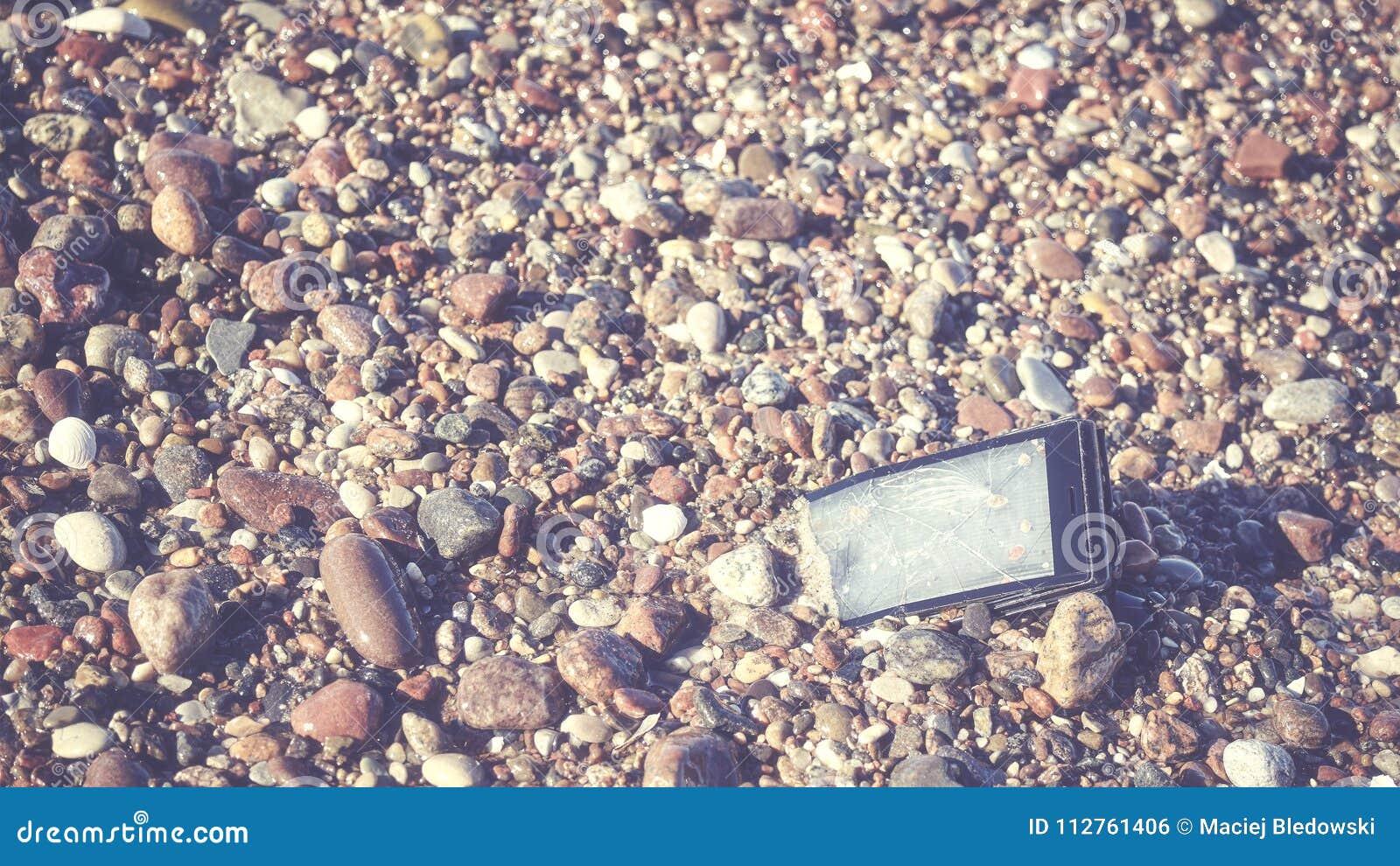 Broken mobile phone on a stony beach.