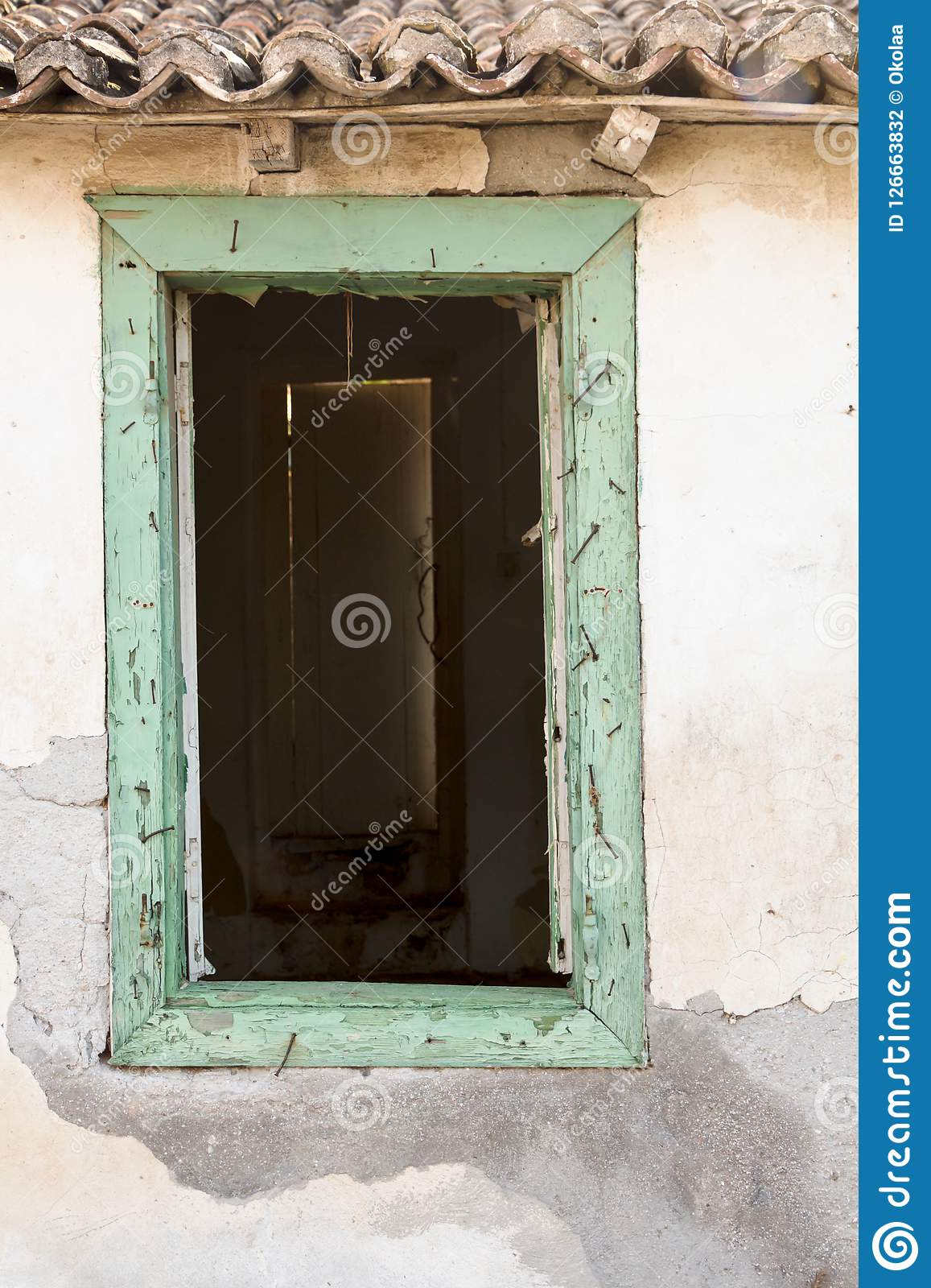 Broken old wooden window on weathered wall.