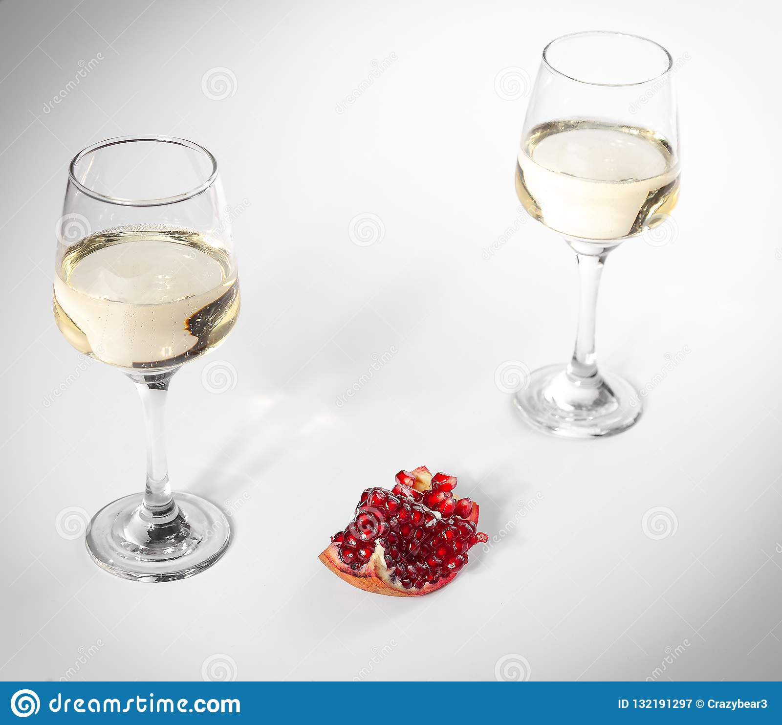 Broken pomegranate lies on a white plate. Two glasses of white wine