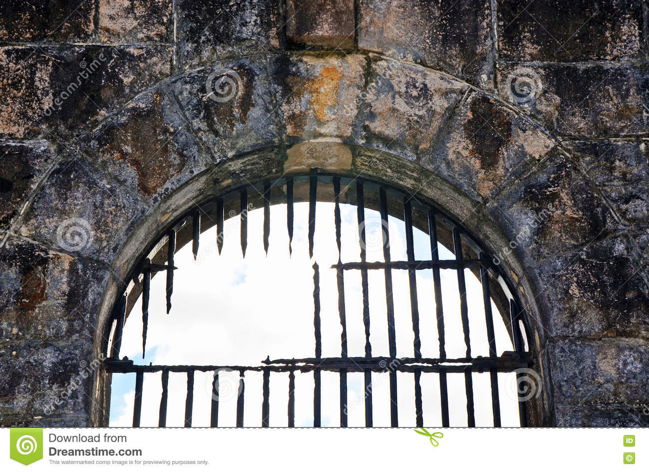 Broken rusty iron bars on old jail (gaol) arched window