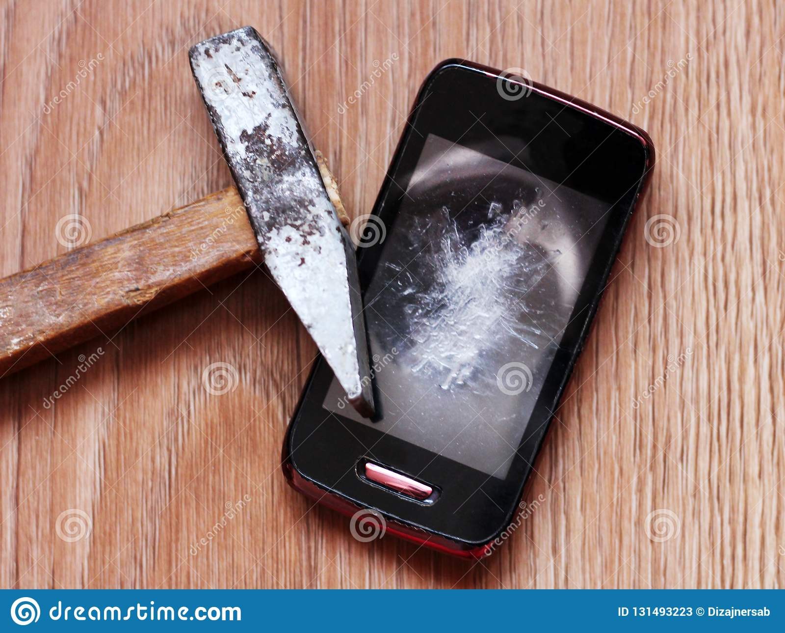 Broken smartphone with cracked screen with hummer on wooden background