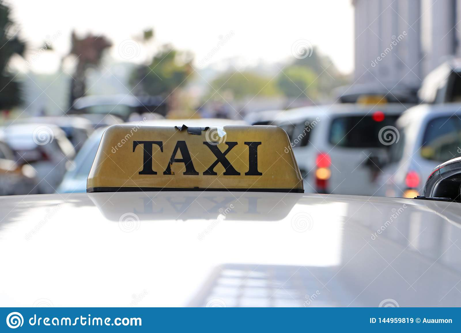 Broken taxi light sign or cab sign in drab yellow color with black text on the car roof at the street blurred background