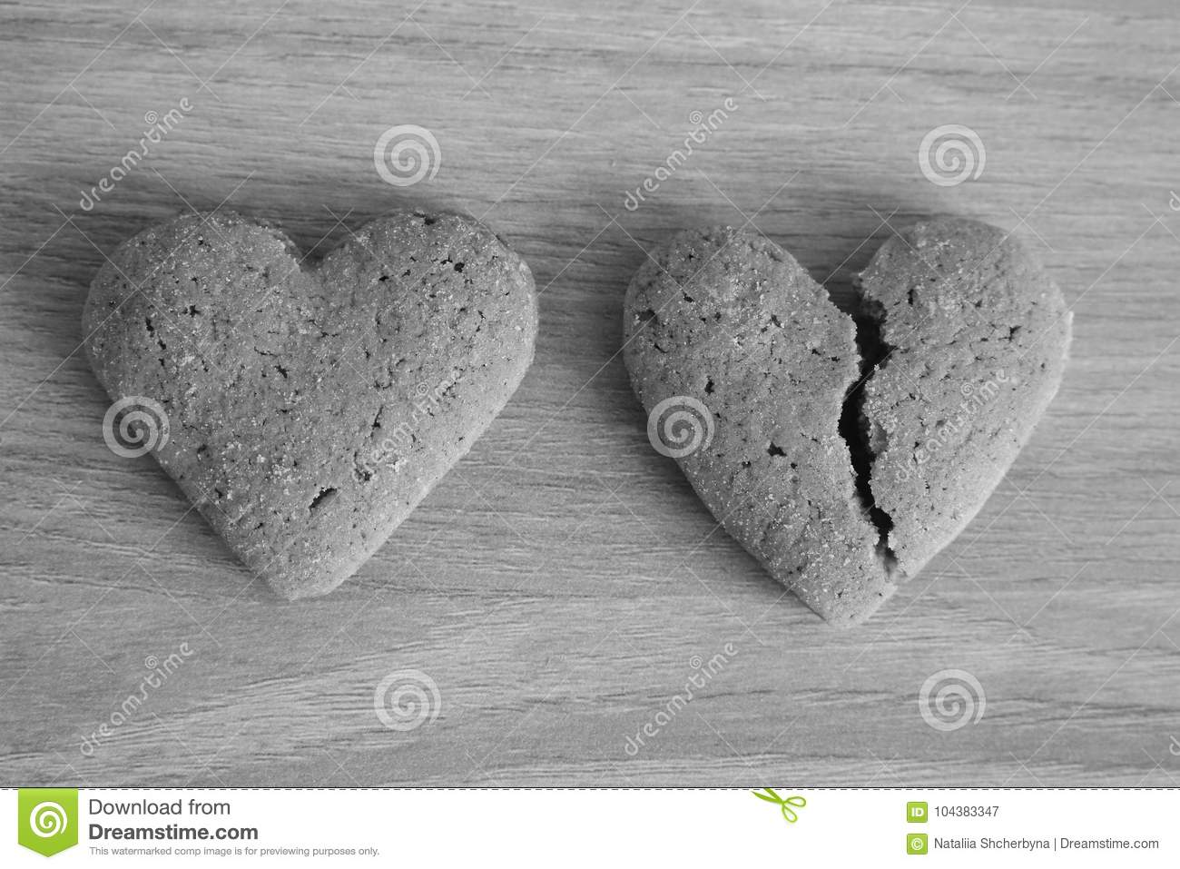 Broken and unbroken shortbread hearts on wooden background black and white as unhappy love background.