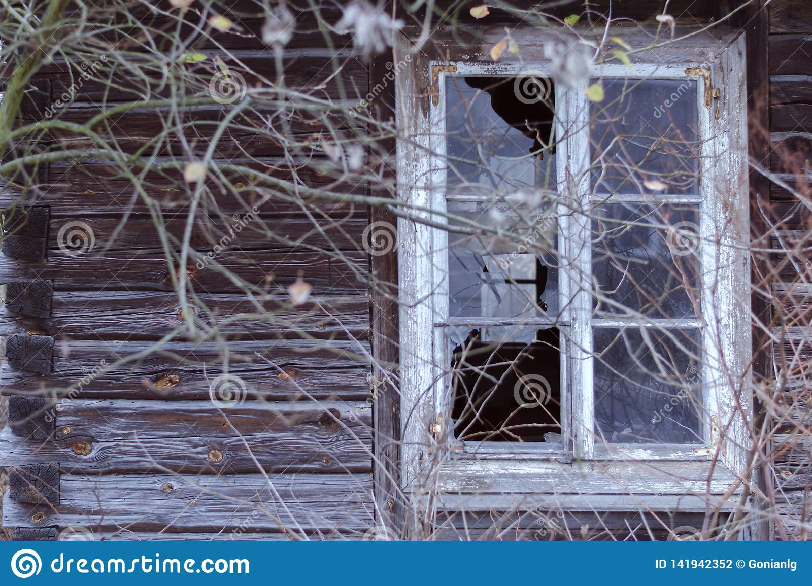 Broken window in an abandoned wooden house. The concept