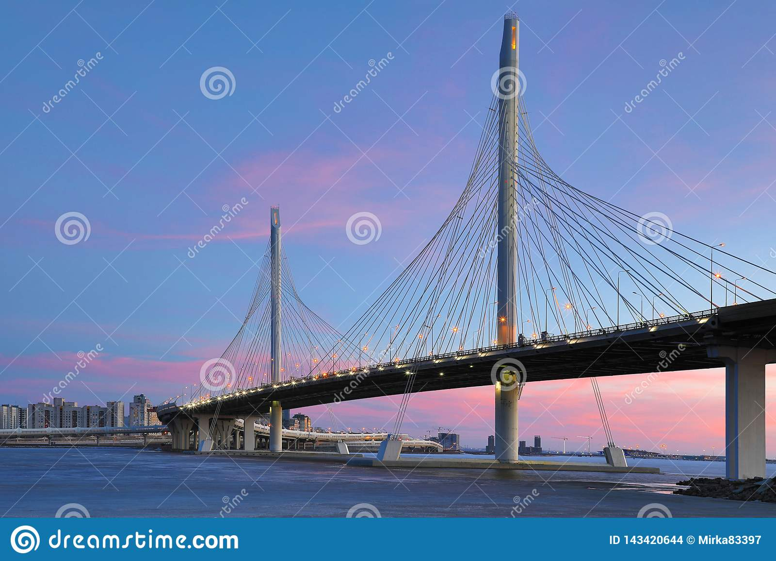 Bron av cirkelhuvudv?gv?gen ?ver den Neva floden n?ra munnen av den i den bl?a timmen efter solnedg?ngen