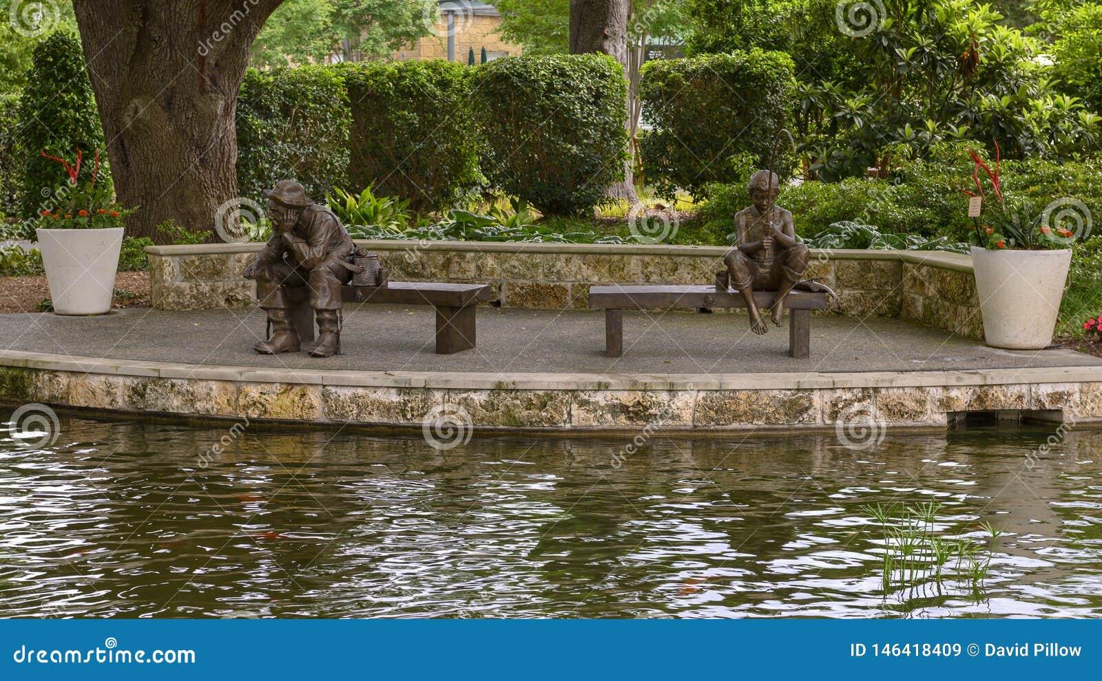 Brons skulptur av ett pojke- och gamal manfiske av Gary Price på Dallas Arboretum och botaniska trädgården