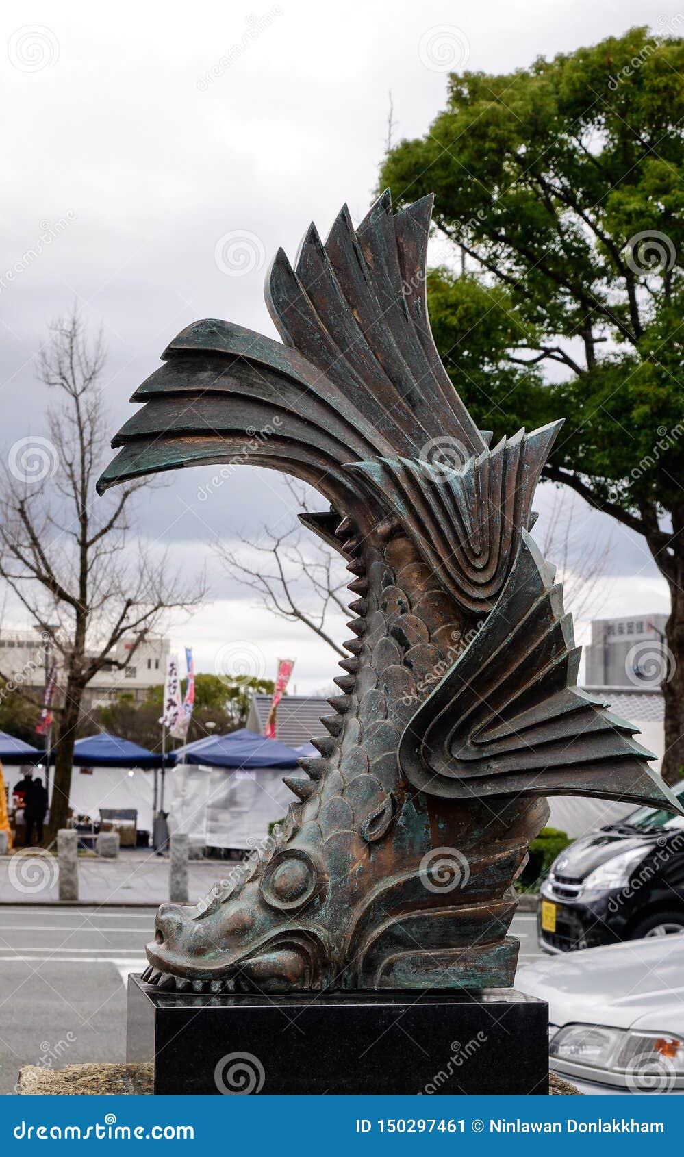 Brons statyn av fisken på gatan
