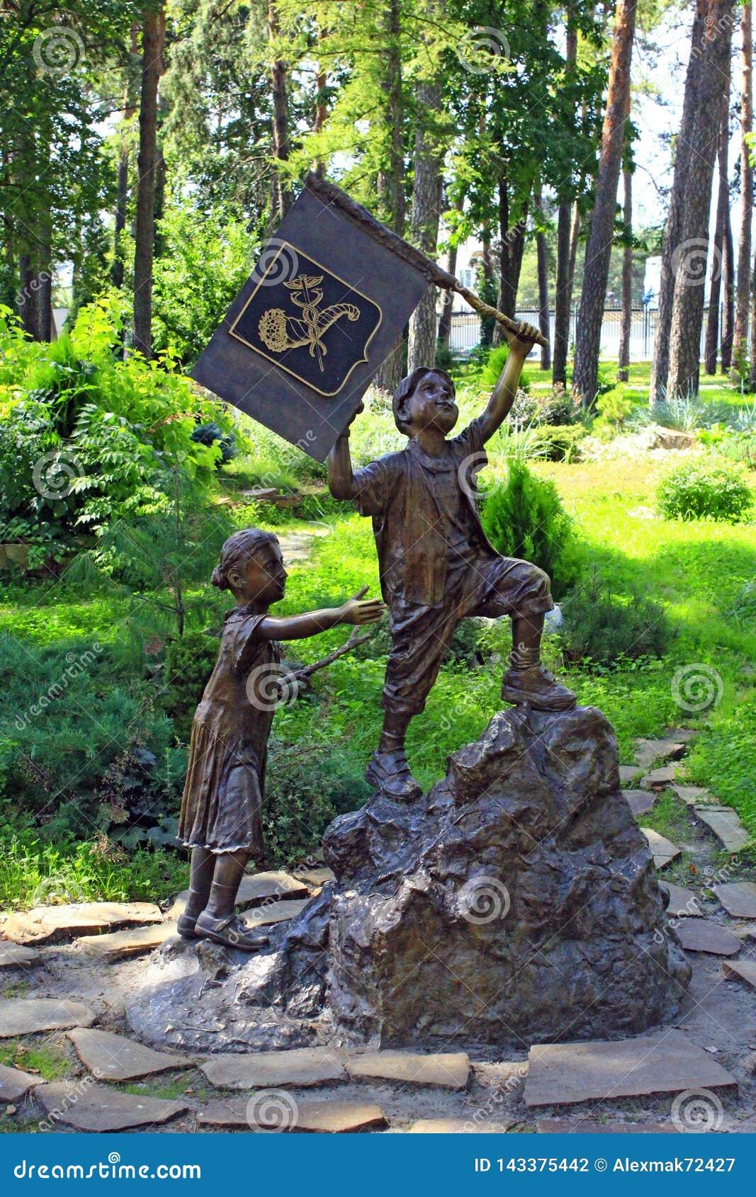 Bronsbeeldhouwwerk van weinig jongen met vlag en meisjes het uitgaan berg in stadspark