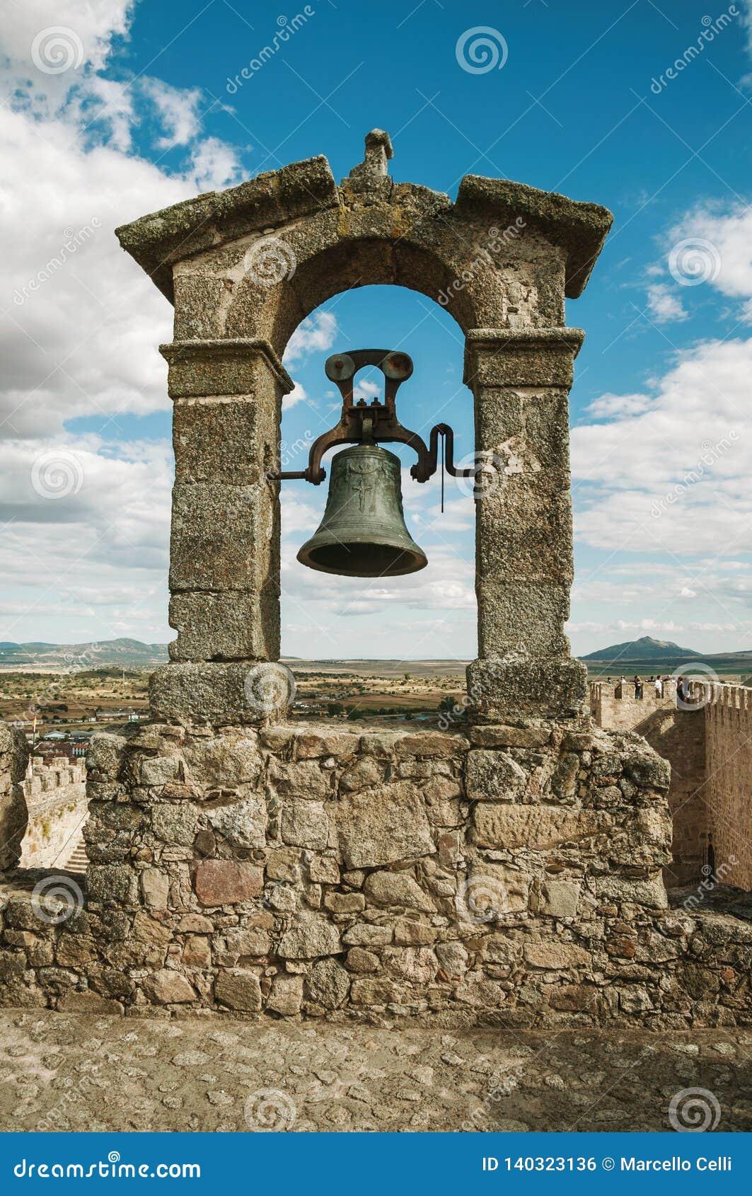 Bronsklok bovenop steenmuur bij het Kasteel van Trujillo
