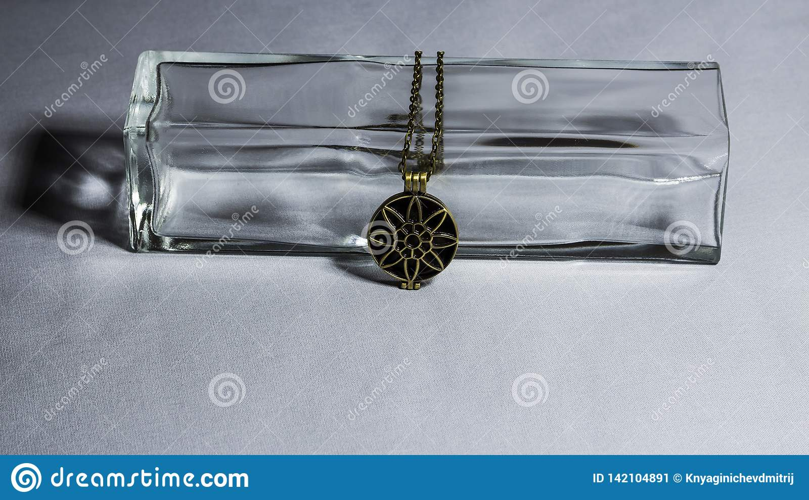 Bronze pendant on the background of a glass vase
