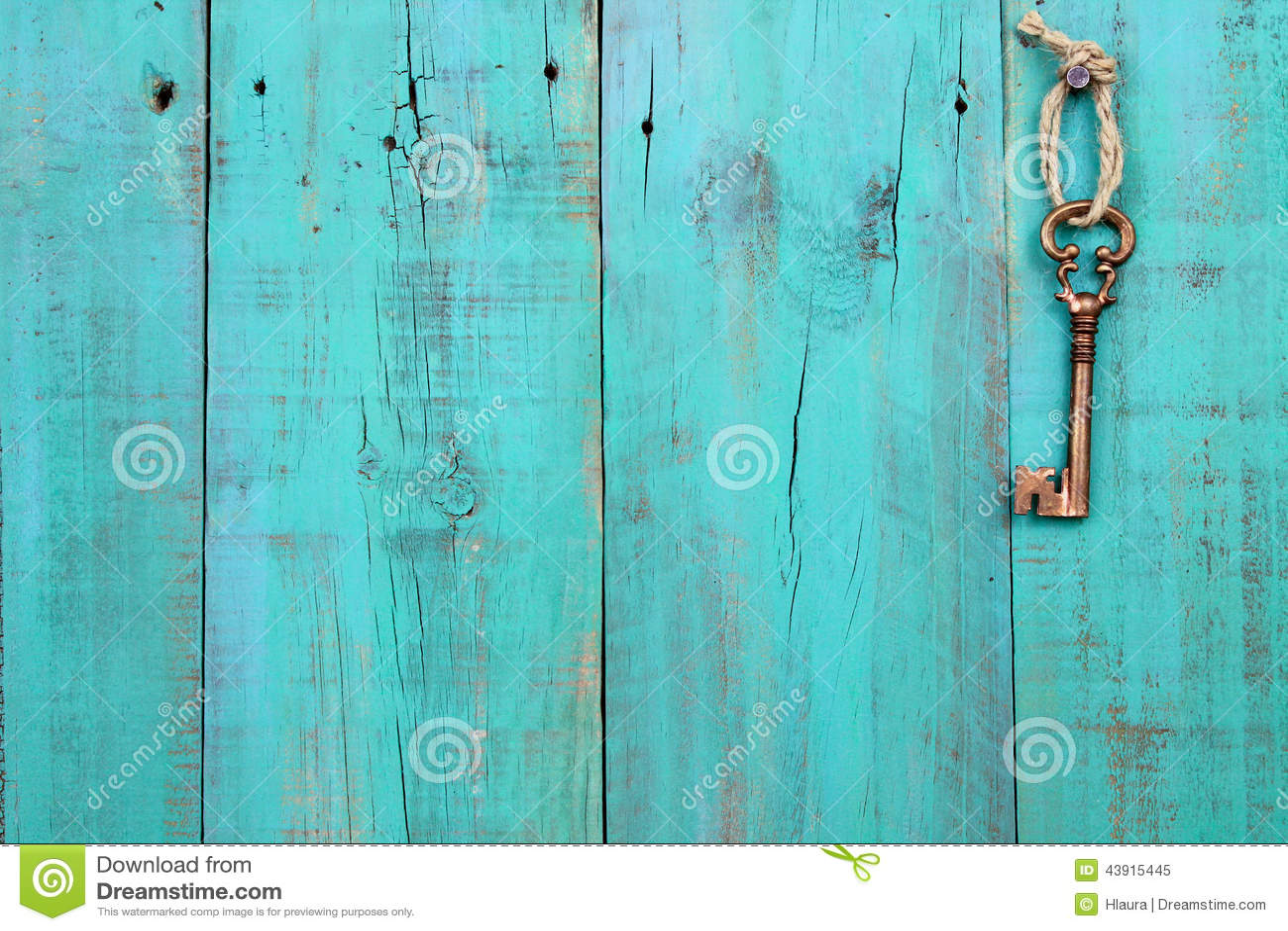 Bronze skeleton key hanging on vintage teal blue wood door