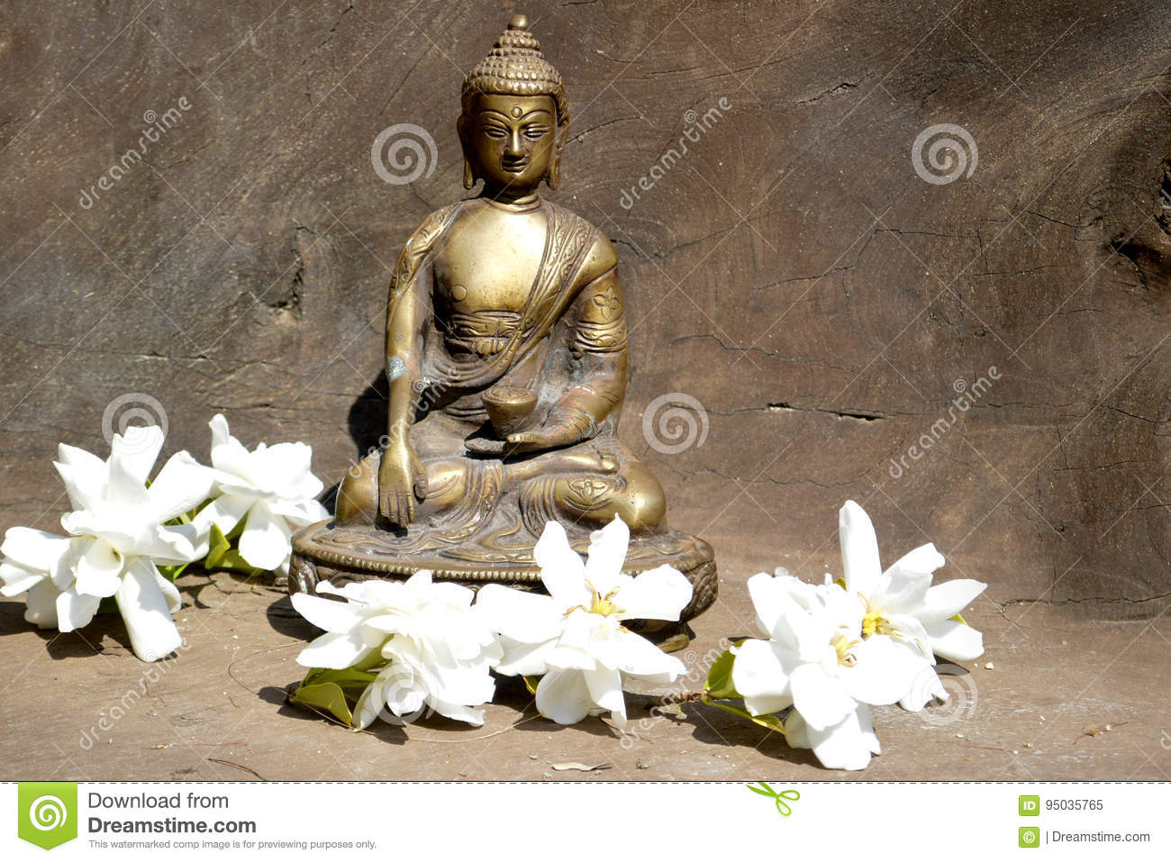 Bronze statue of Touching earth Buddha on wood with white flowers