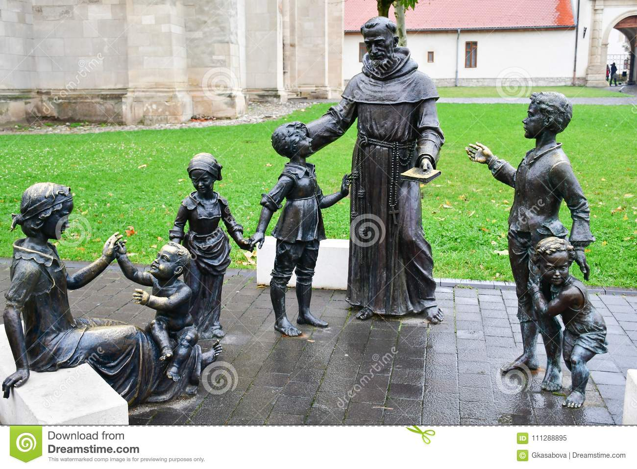 Bronze statue of woman,priest and kids