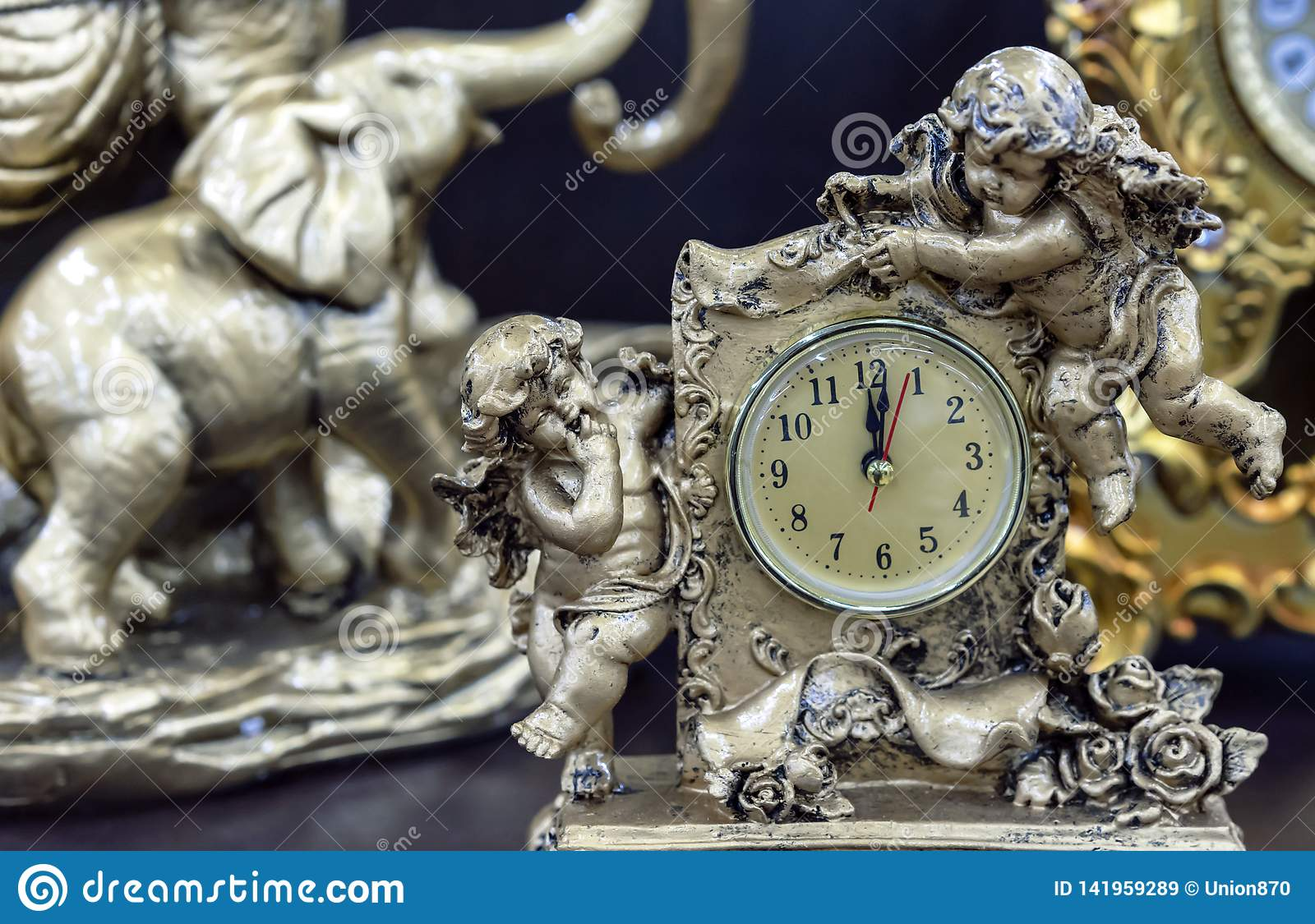 Bronze table clock with angels on a wooden table