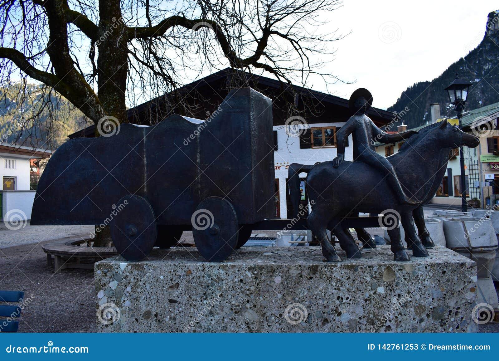 Bronzestatue in Oberammergau, das einen Wagen zeigt