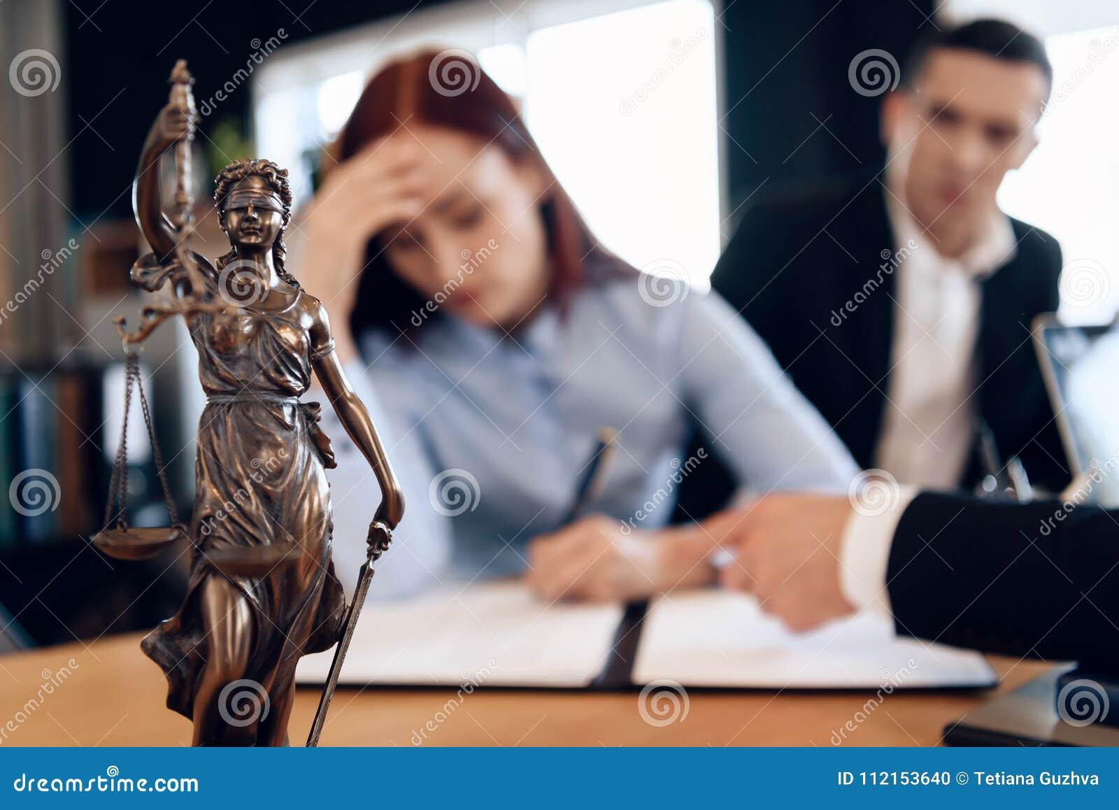 Bronzestatue von Themis hält Skalen von Gerechtigkeit In unfocused Hintergrund unterzeichnet Paar Dokumente