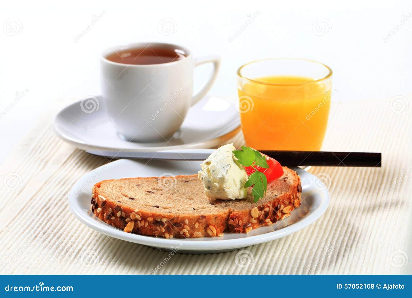 Brood met uitgespreide kaas, kop thee en jus d orange
