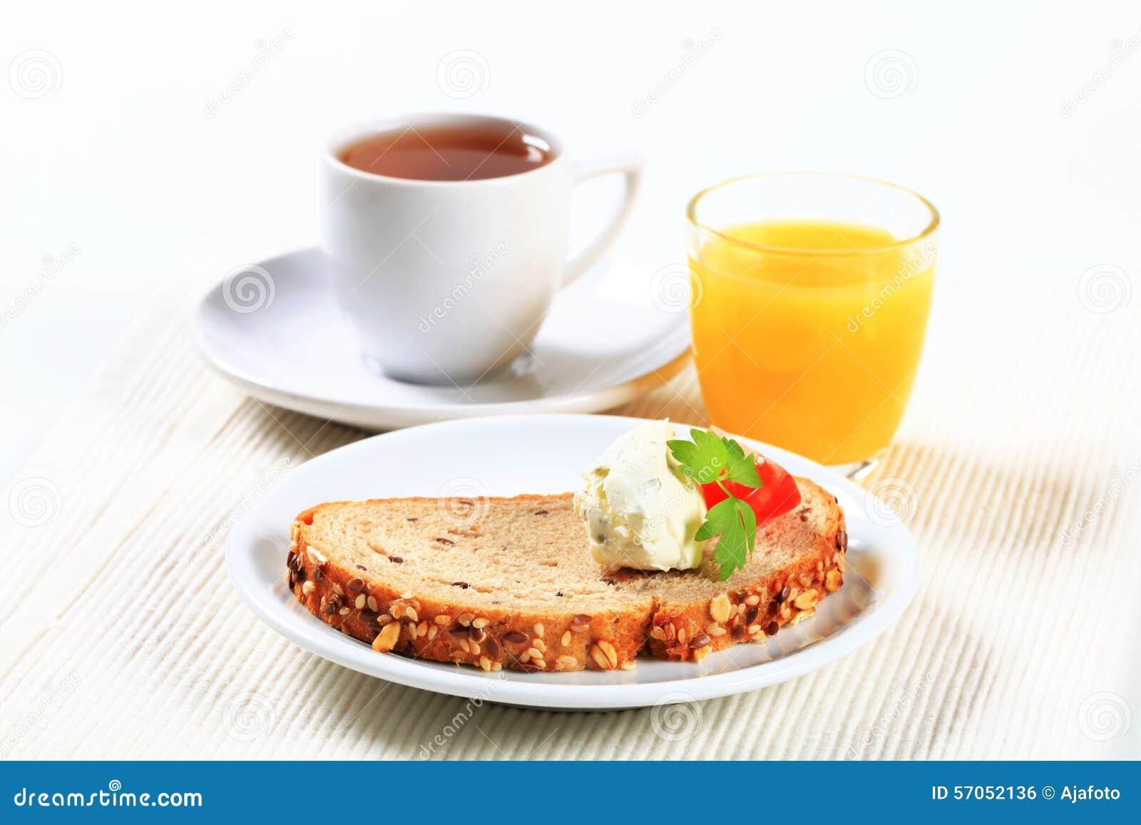Brood met uitgespreide kaas, thee en jus d orange