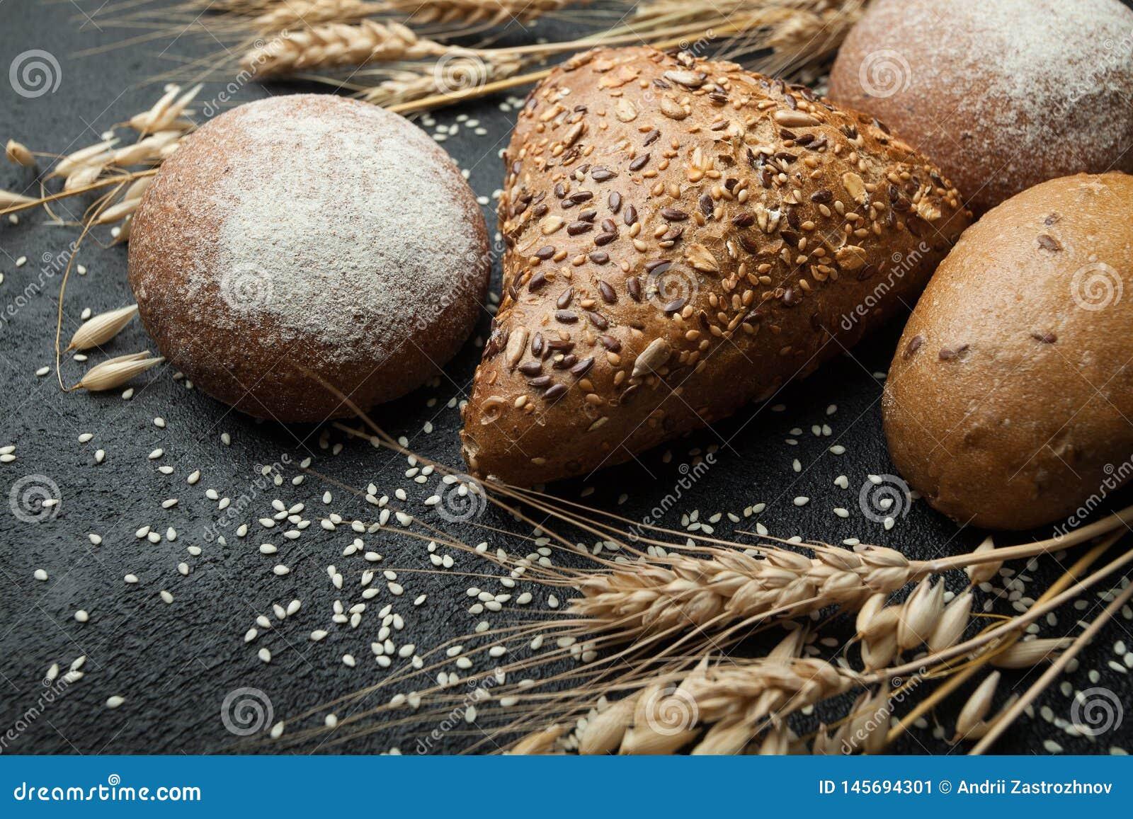 Brood van verschillende soorten op een donkere raad met aartjes van tarwe, rogge en haver Koolhydraten en dieet