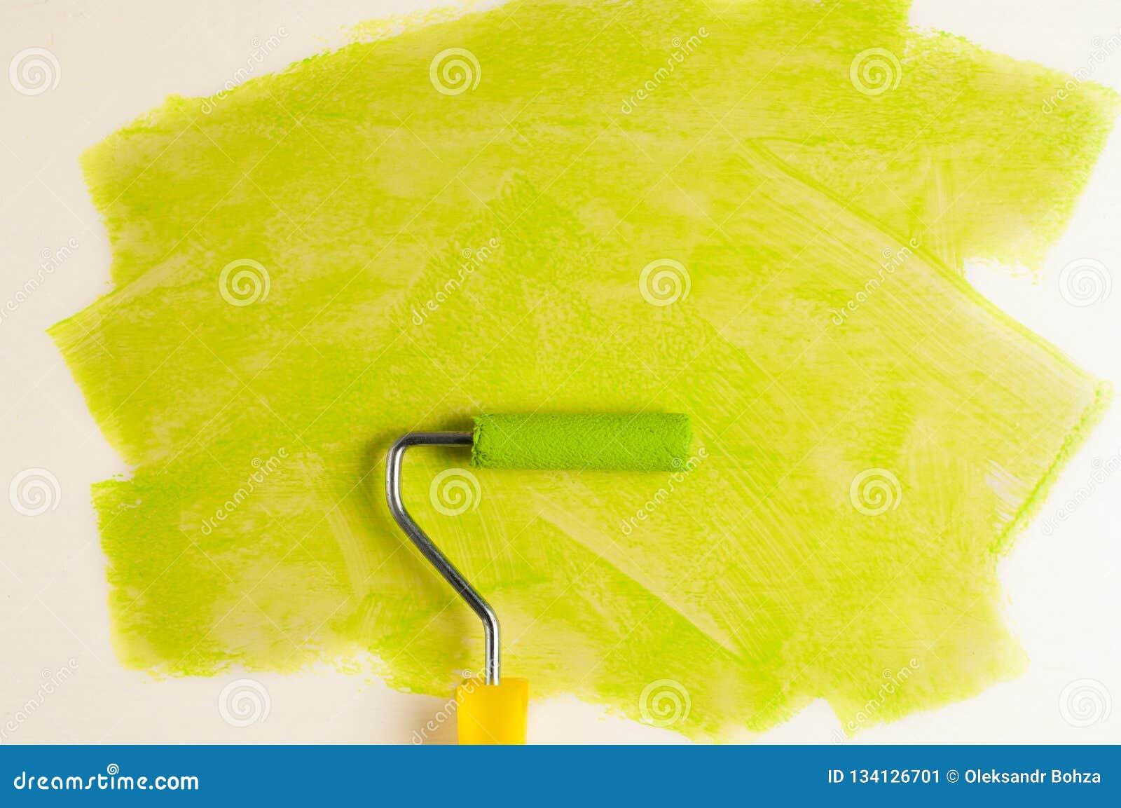 Broodje voor verf en groen spoor op muur Het concept van de reparatie