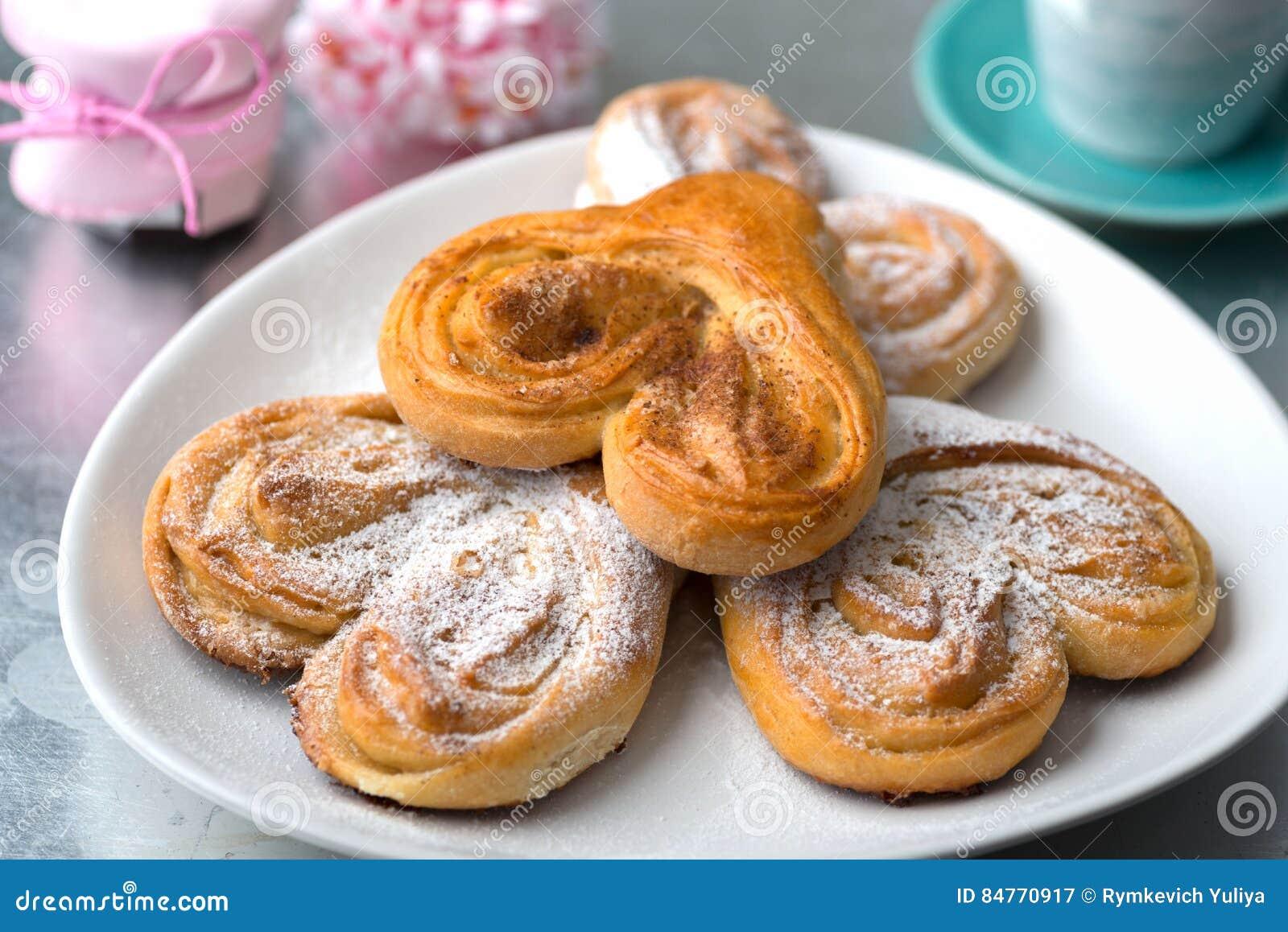 Broodjes in de vorm van hart met kaneel en gepoederde suiker met