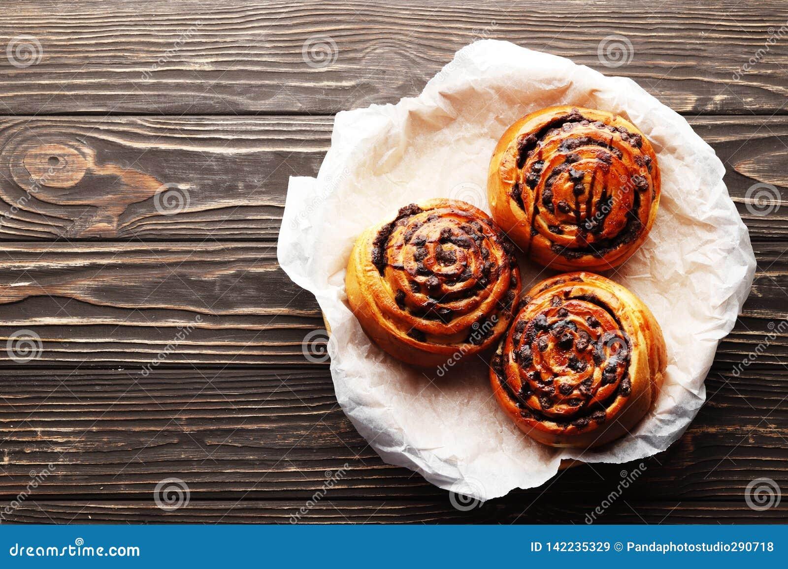 Broodjes met kaneel en chocolade op een bruine houten achtergrond