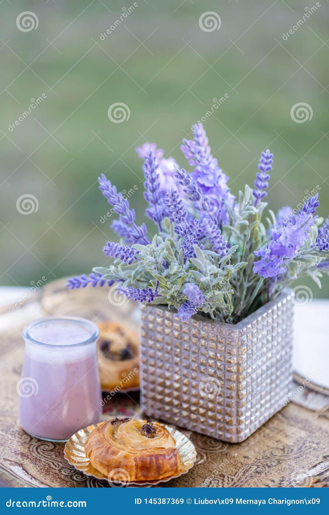 Broodjes met rozijnen en bosbessenyoghurt in glaskruiken zomer Boeket van bloemenlavendel