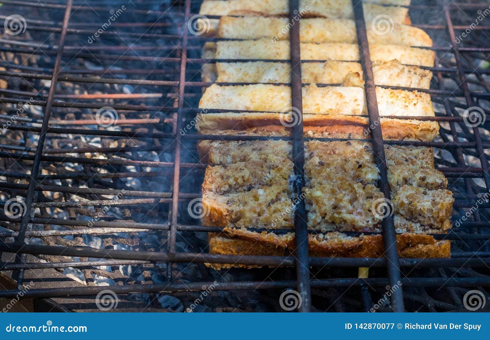 Broodjies surafricanos tradicionales del braai preparados en los carbones abiertos