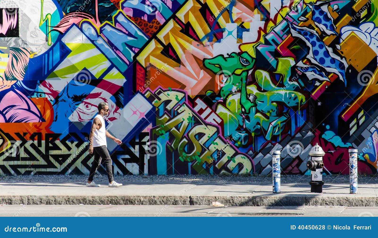 BROOKLYN, NYC, US, October 1 2013: Street art in Brooklyn. Hipster male walking next to a wall of graffiti in Brooklyn, New