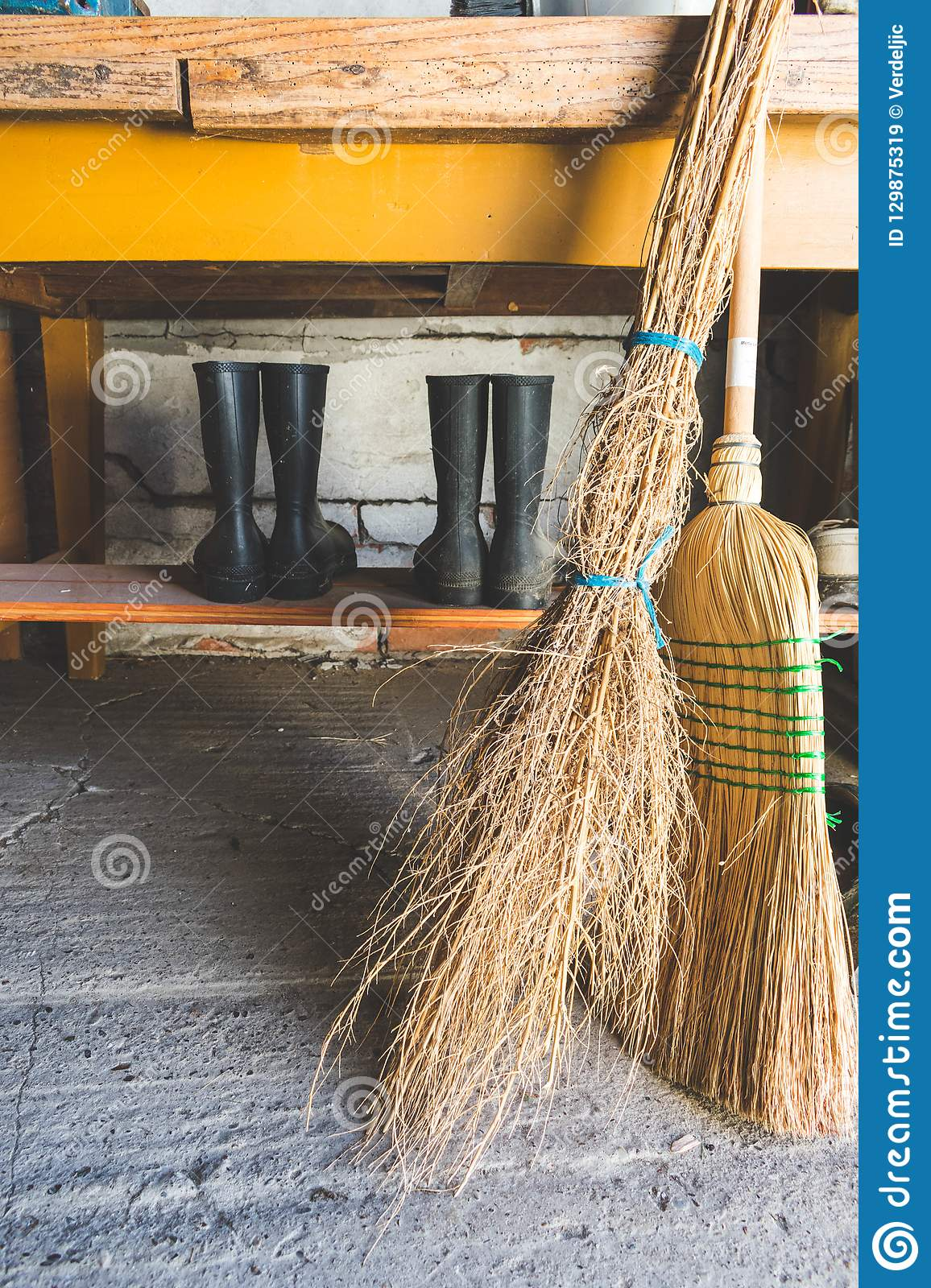 Broom And Besom Against A Wooden Table And Two Rubber Boots