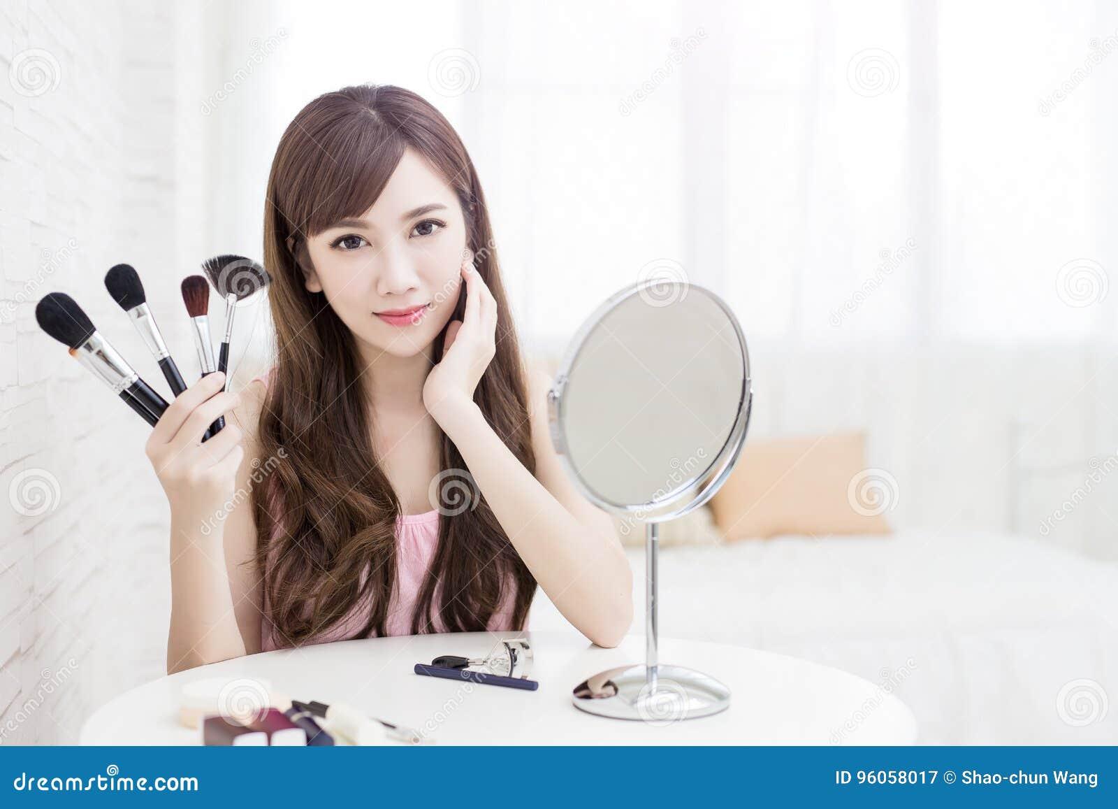 Brosse de maquillage de prise de femme
