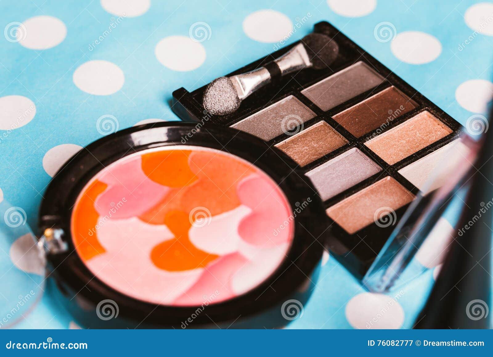Brosse et cosmétiques de maquillage sur la table en bois bleue