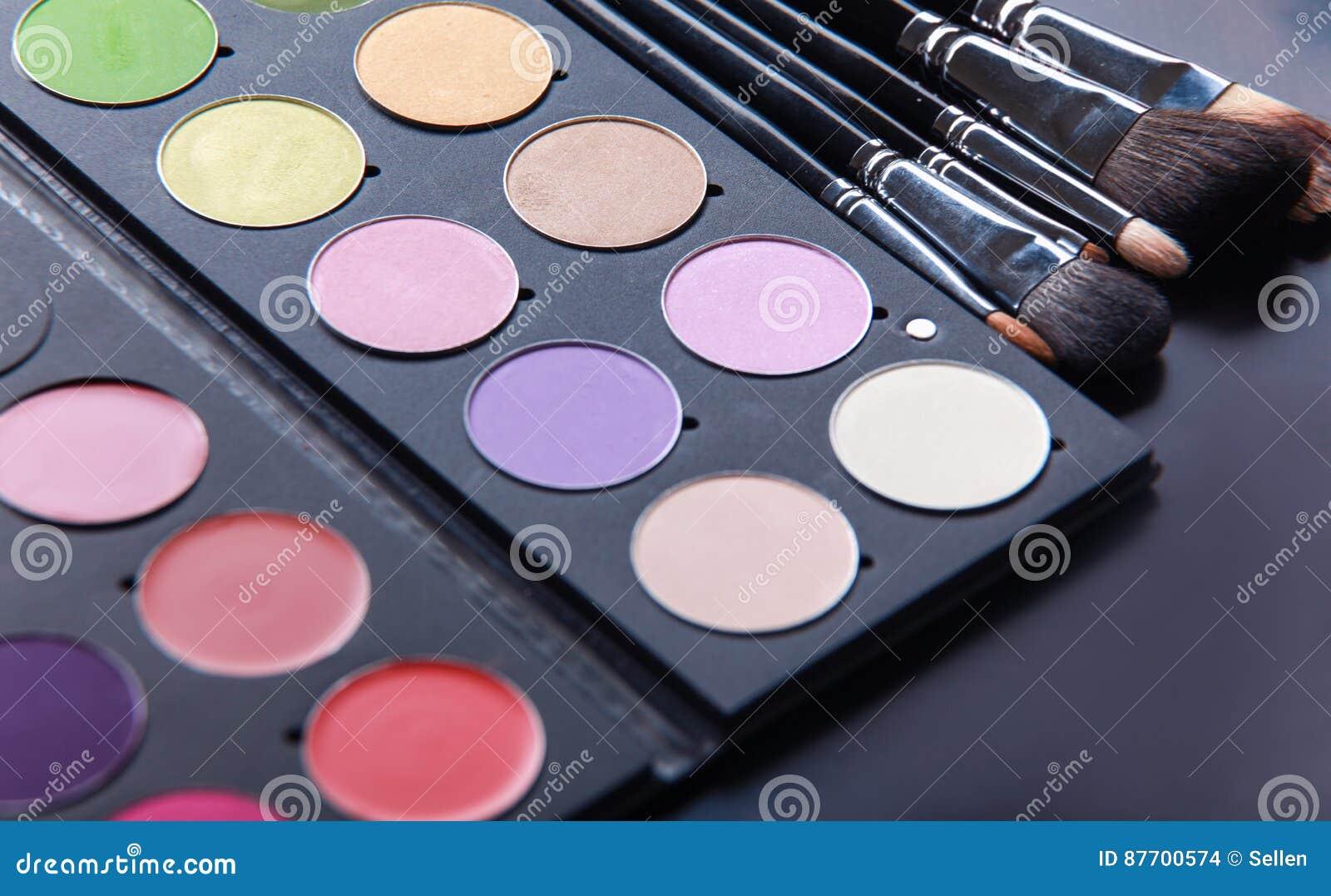 Brosses de maquillage et fards à paupières de maquillage sur le bureau