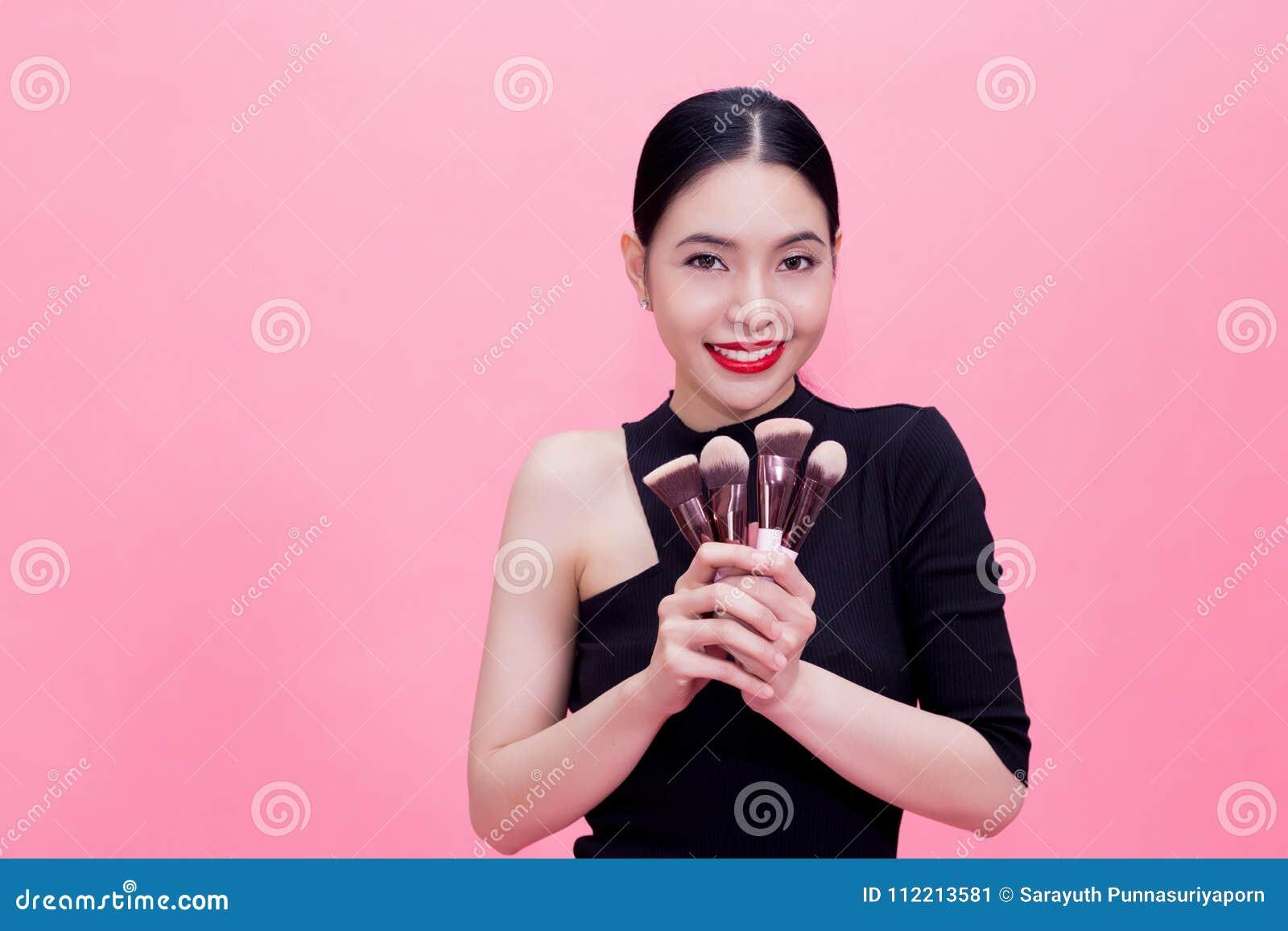 Brosses de transport de maquillage de jeune femme asiatique élégante en main avec c