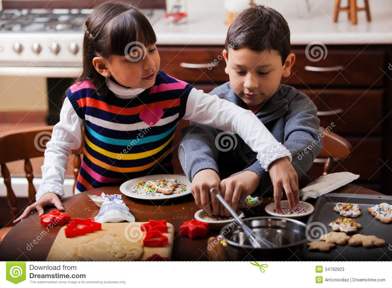 Brother and sister baking cookies stock photos image for Baking oranges for christmas decoration