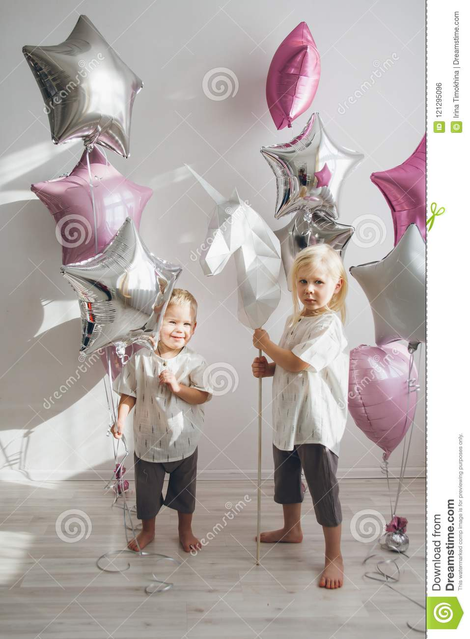Brother and sister holding balloons