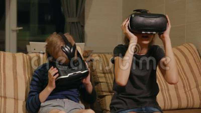 93c4cd06cffc Brother with sister at home sitting on the couch playing the game using virtual  reality glasses. Happy family. Indoors